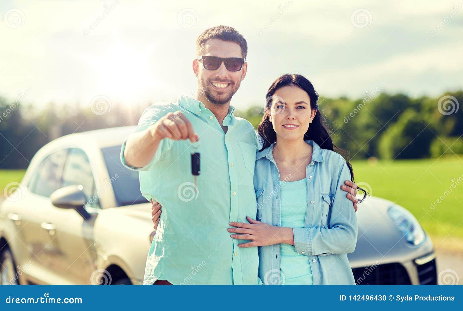 Hombre y mujer felices con el abrazo dominante del coche