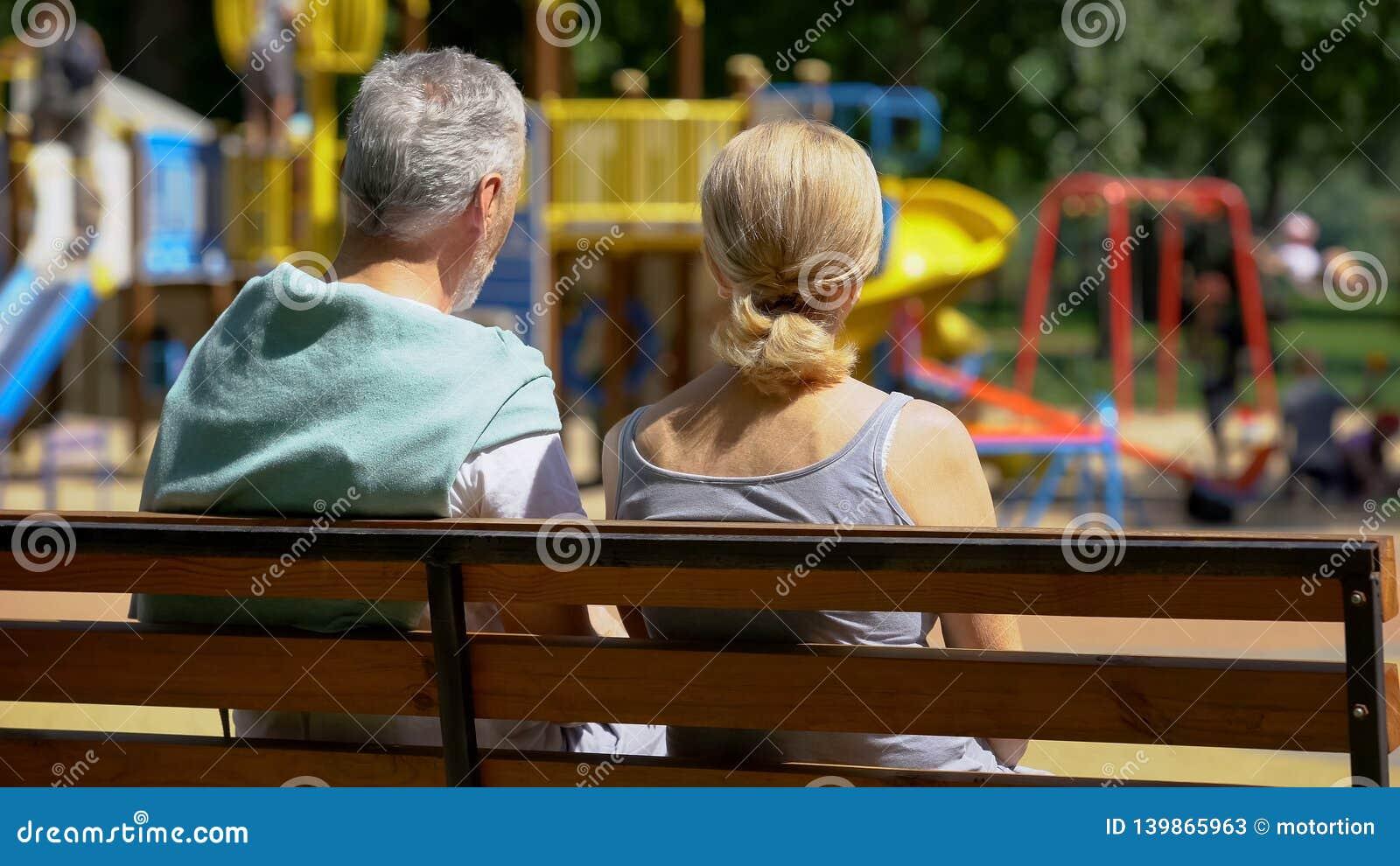 Hombre y mujer jubilados en banco en los nietos de observación del parque, memorias felices