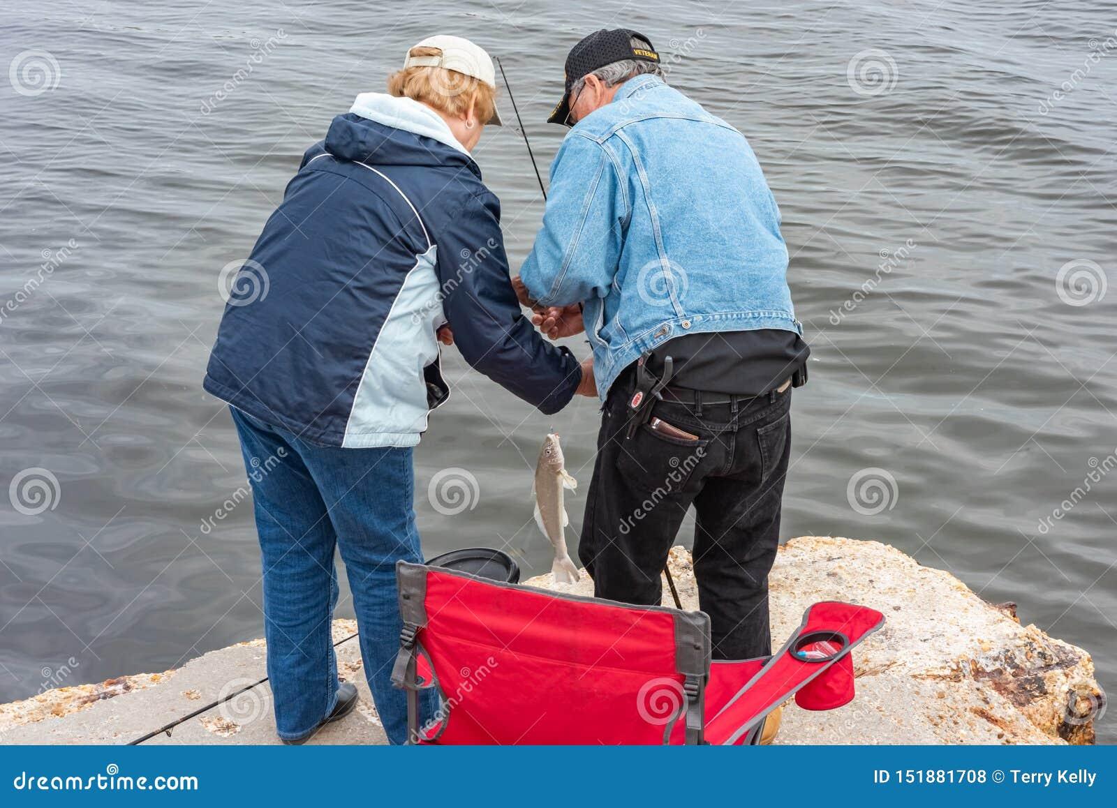 Hombre y mujer que cogen un pescado