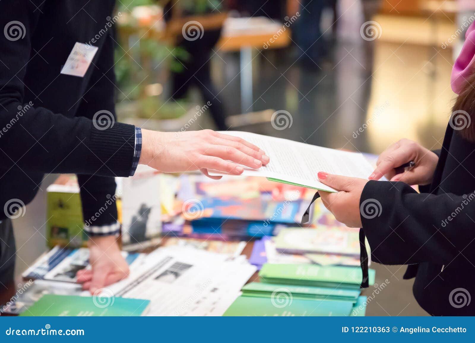 Hombre y mujer que comparten el prospecto de la información sobre soporte de la exposición