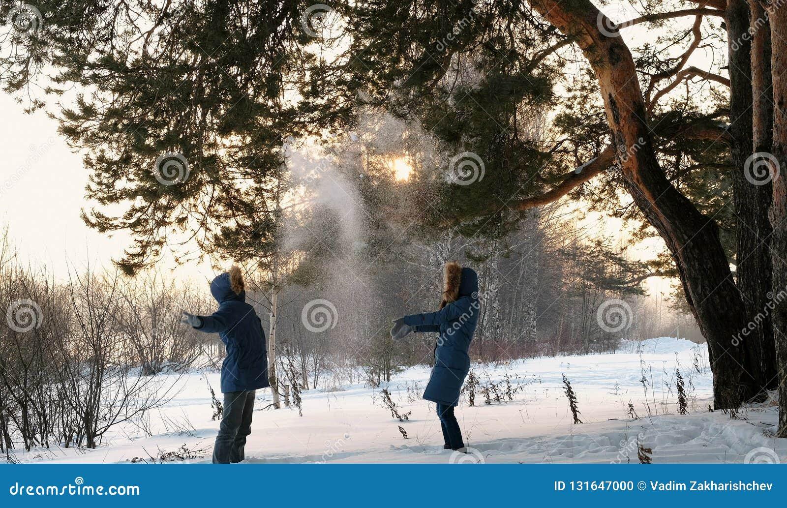Hombre y mujer que juegan bolas de nieve en la puesta del sol del bosque del invierno en el bosque del invierno