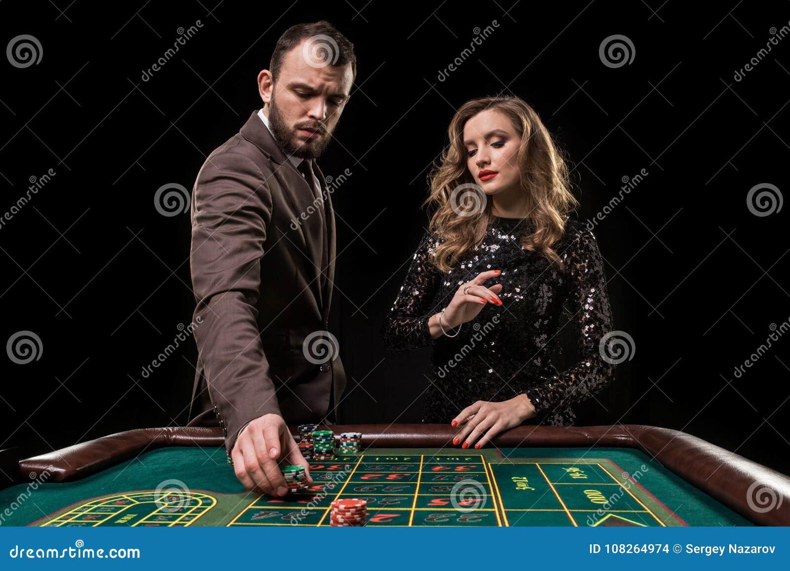 Hombre y mujer que juegan en la tabla de la ruleta en casino