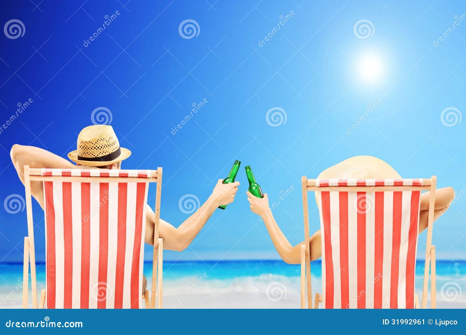 Hombre y mujer que se relajan en una playa y que animan con las cervezas