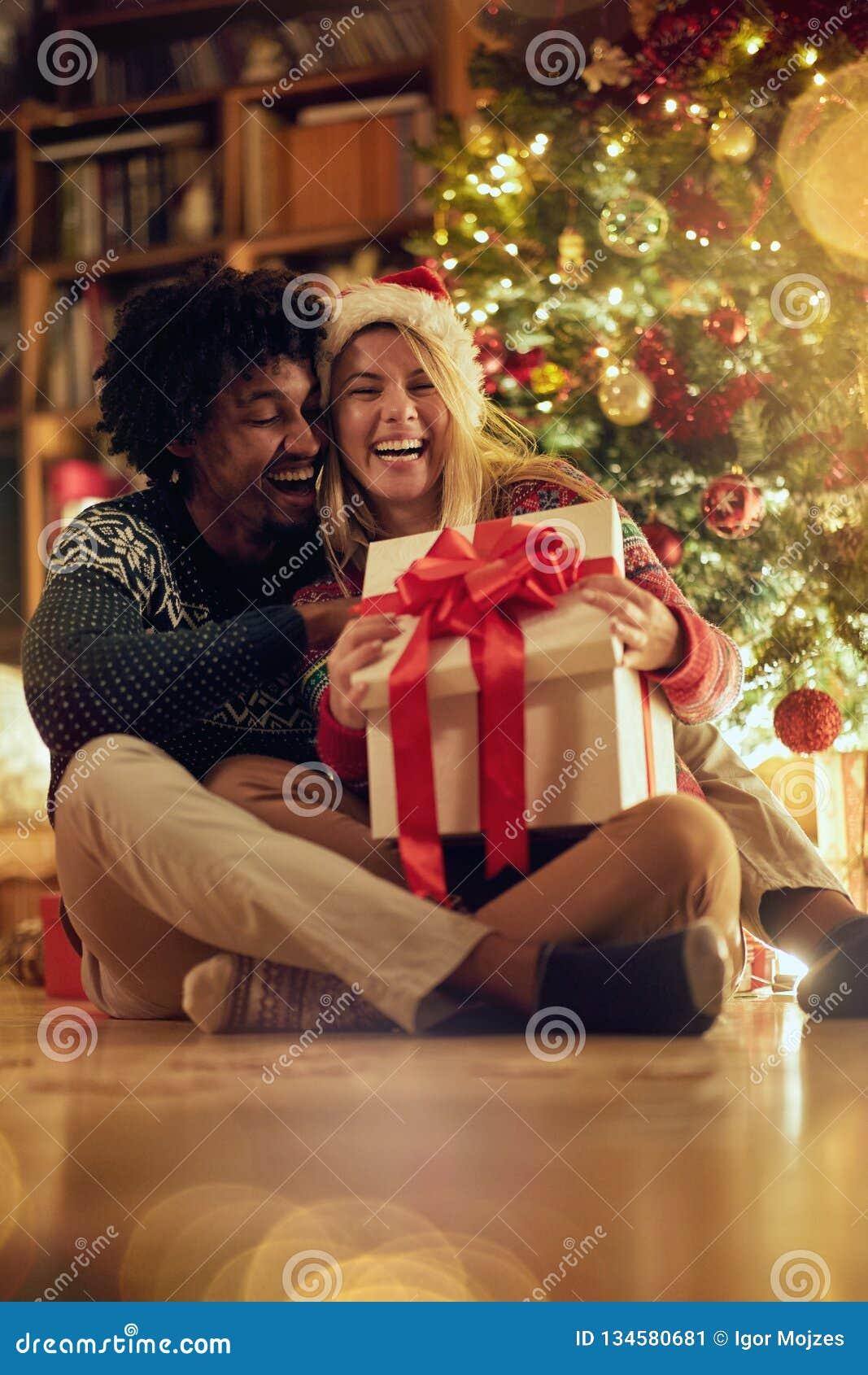 Hombre y mujer sonrientes que intercambian regalos de Navidad