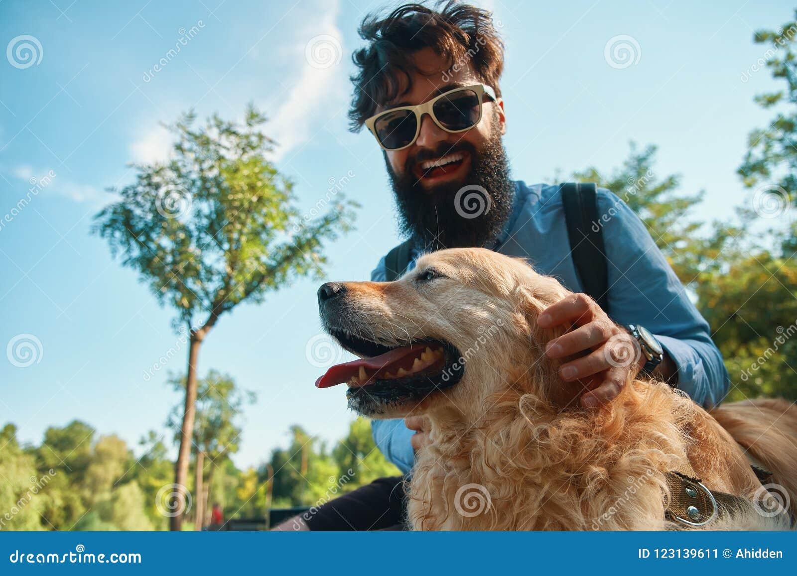 Hombre y perro que se divierten, el jugar, haciendo caras divertidas mientras que restin