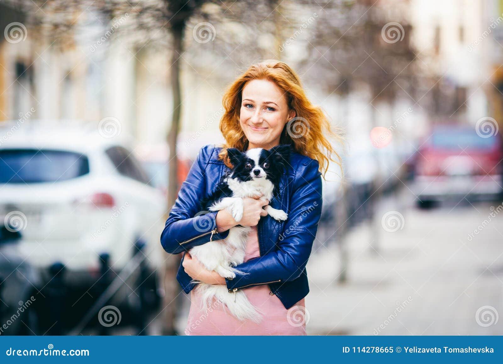 Hombre y perro sujetos mujer caucásica pelirroja joven con las pecas en perro lanudo blanco y negro de la raza de la chihuahua de