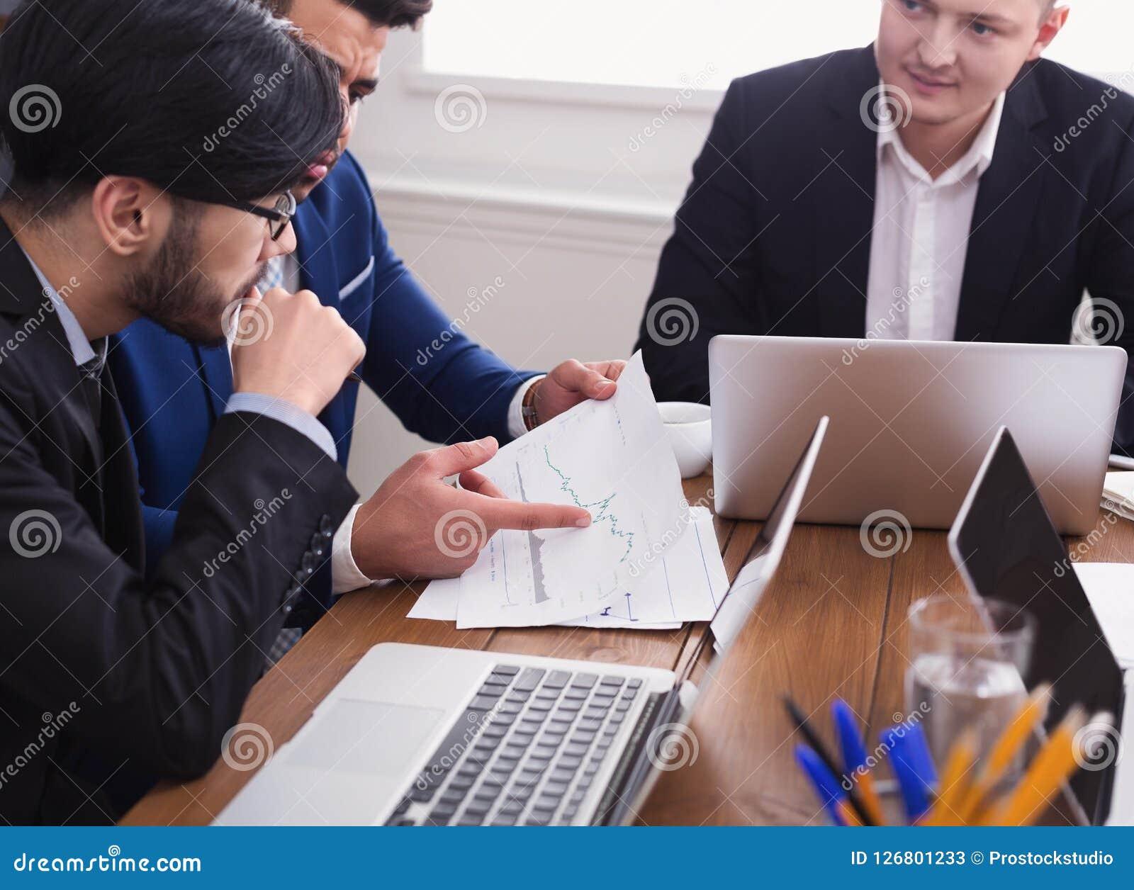 Hombre y socios de negocios que discuten documentos en oficina