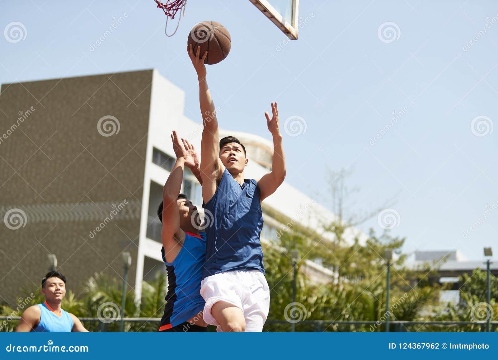 Hombres asiáticos jovenes que juegan a baloncesto