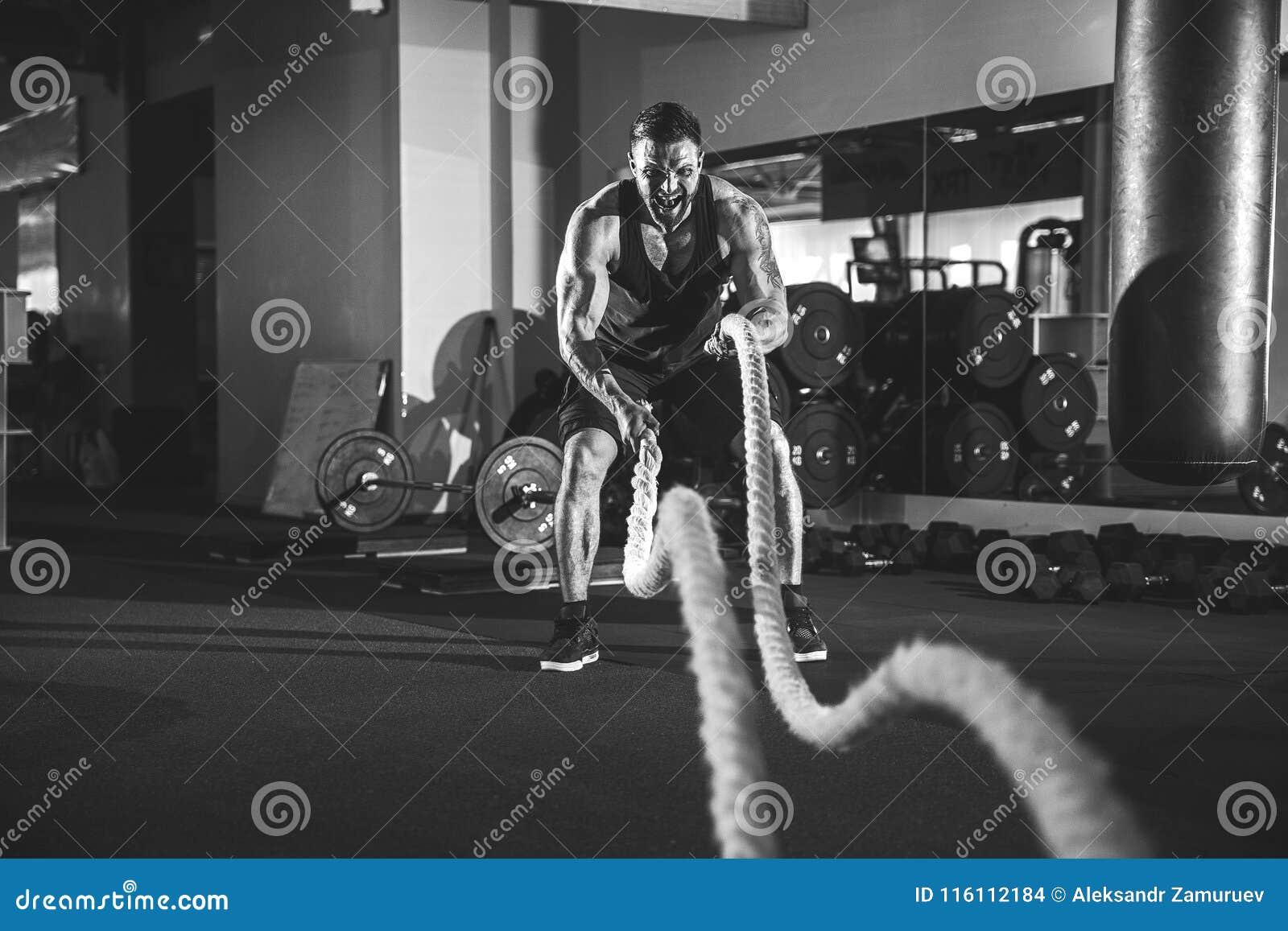 Hombres con la cuerda en gimnasio funcional del entrenamiento