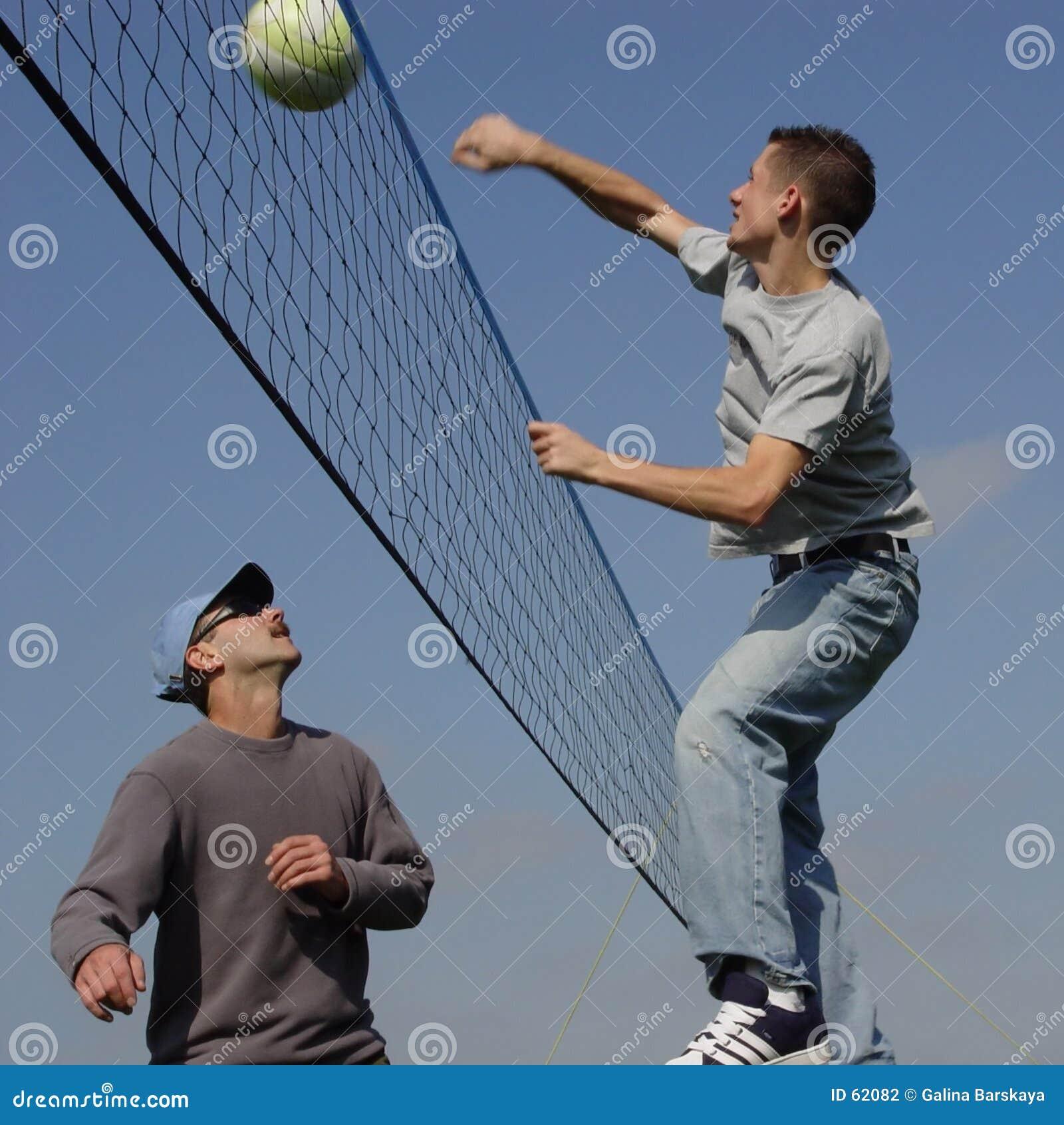 Hombres de los pares que juegan a voleibol