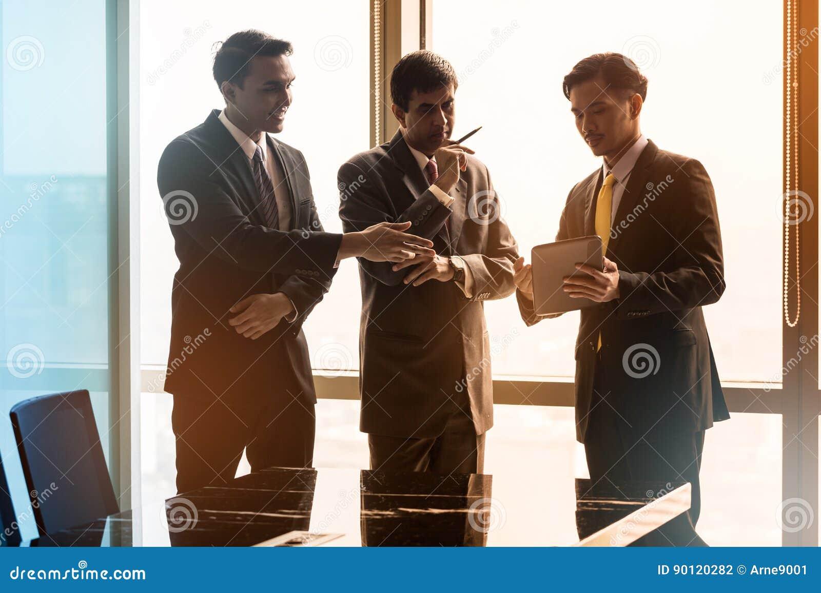 Hombres de negocios asiáticos que tienen conversación en la sala de conferencias