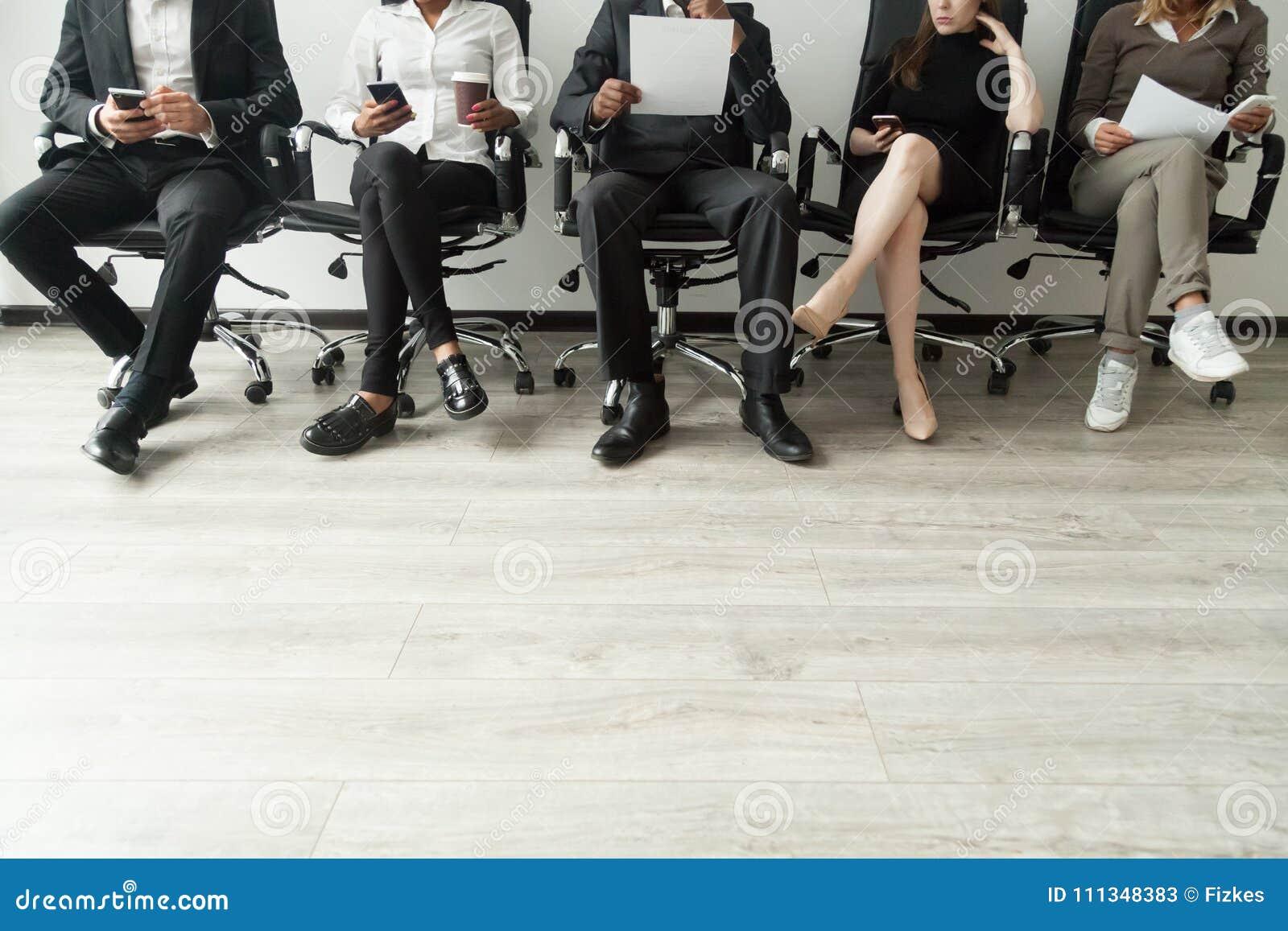 Hombres de negocios diversos que esperan en la cola que sostiene smartphones y