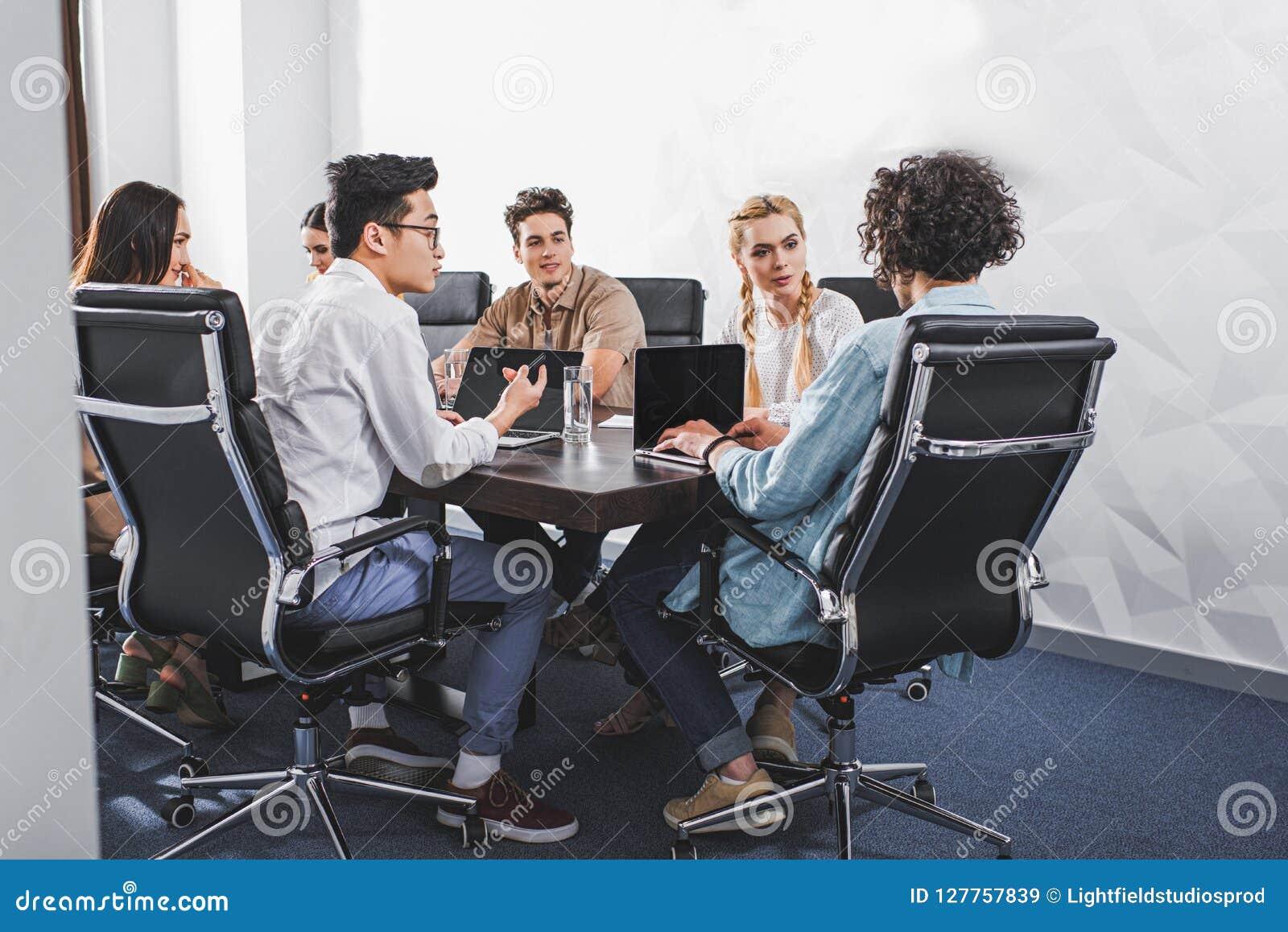 Hombres de negocios multiétnicos que tienen discusión en la tabla con los ordenadores portátiles en moderno