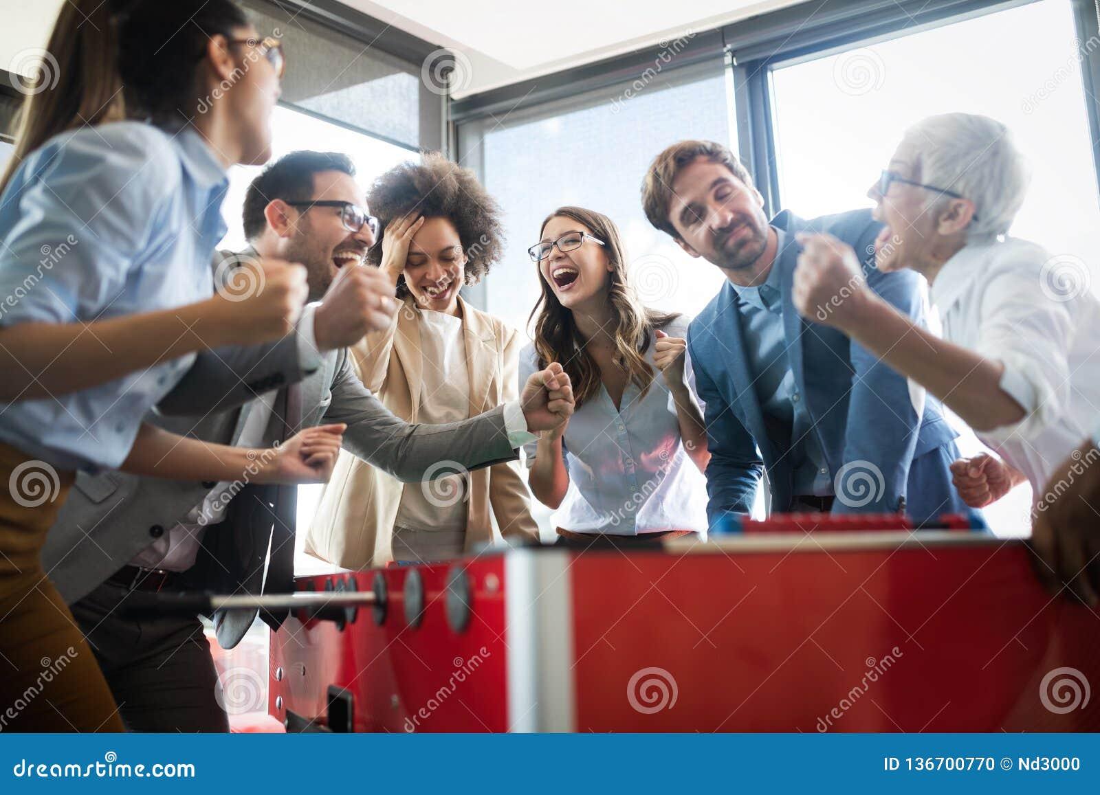Hombres de negocios multiculturales que celebran triunfo mientras que juega a fútbol de la tabla
