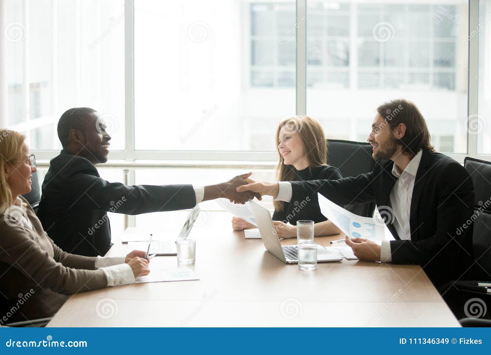 Hombres de negocios multirraciales en apretón de manos de los trajes en el equipo ejecutivo o