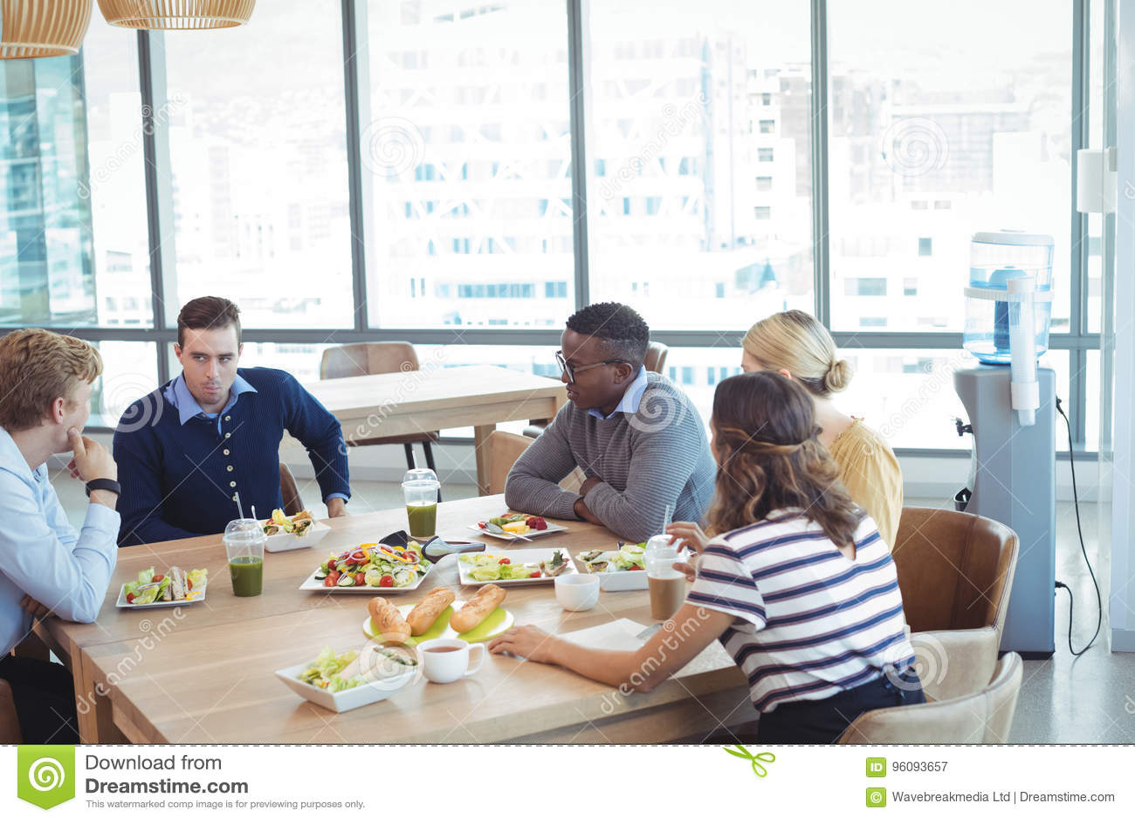 Hombres de negocios que almuerzan en la cafetería de la oficina