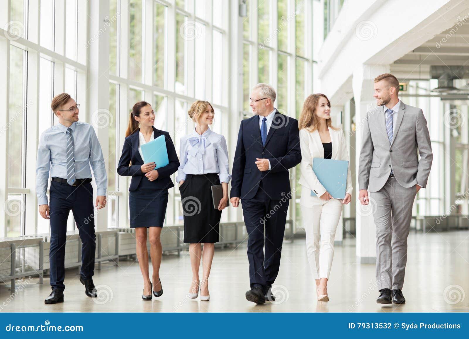 Hombres de negocios que caminan a lo largo del edificio de oficinas