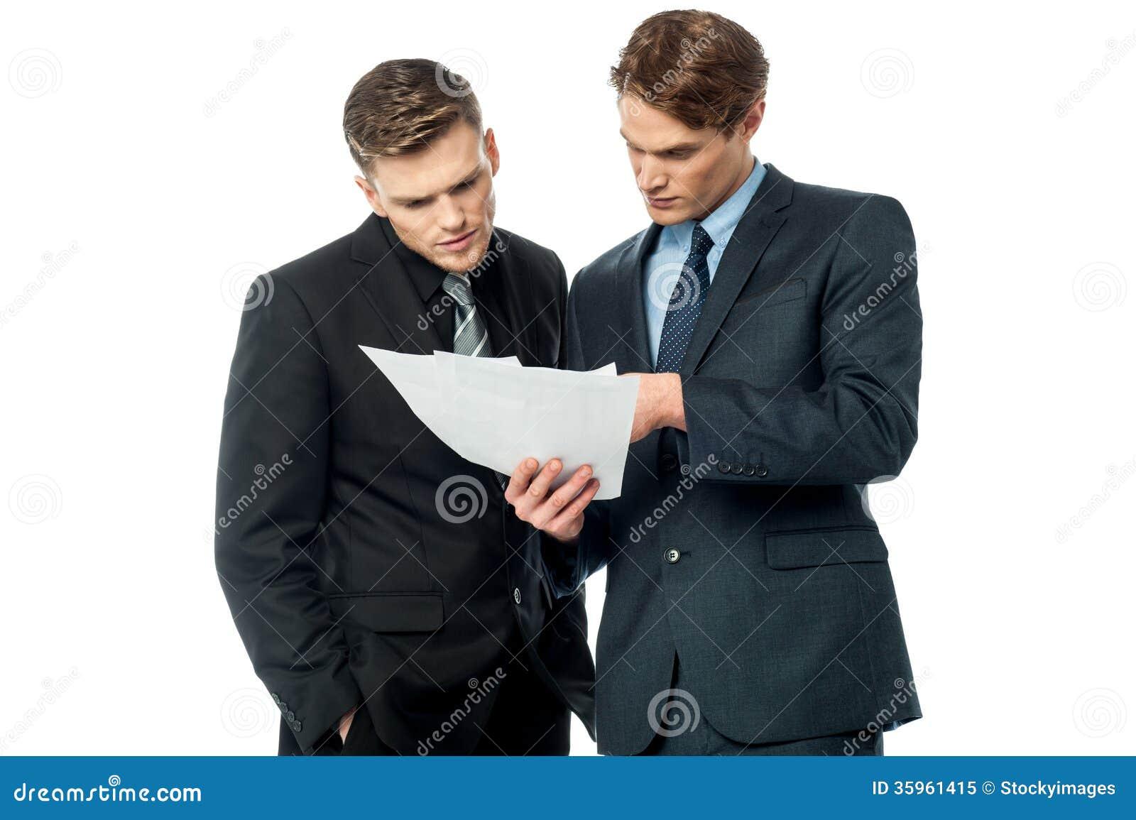 Hombres de negocios que evalúan documentos del trato