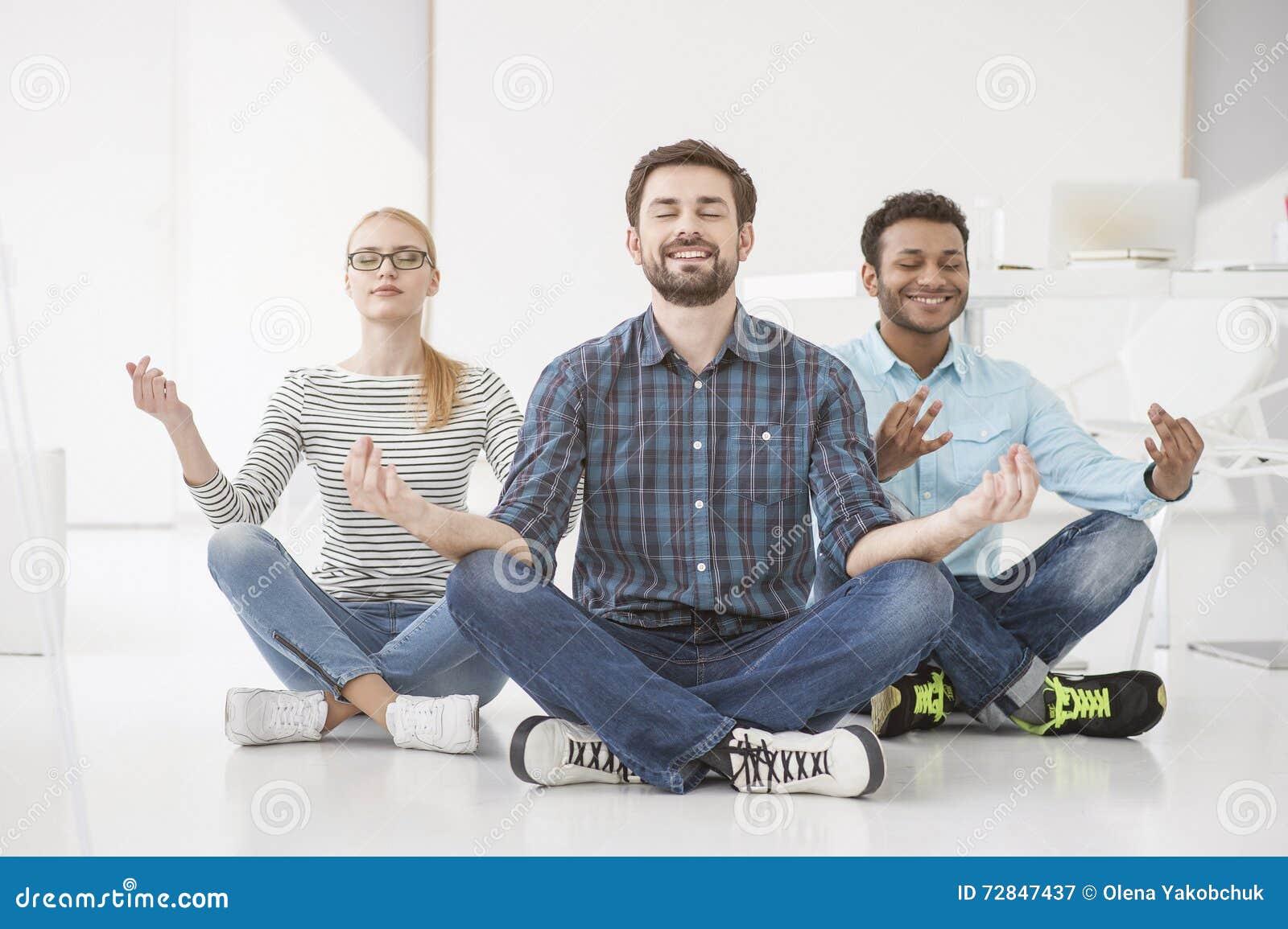 Hombres de negocios que hacen yoga en piso en oficina