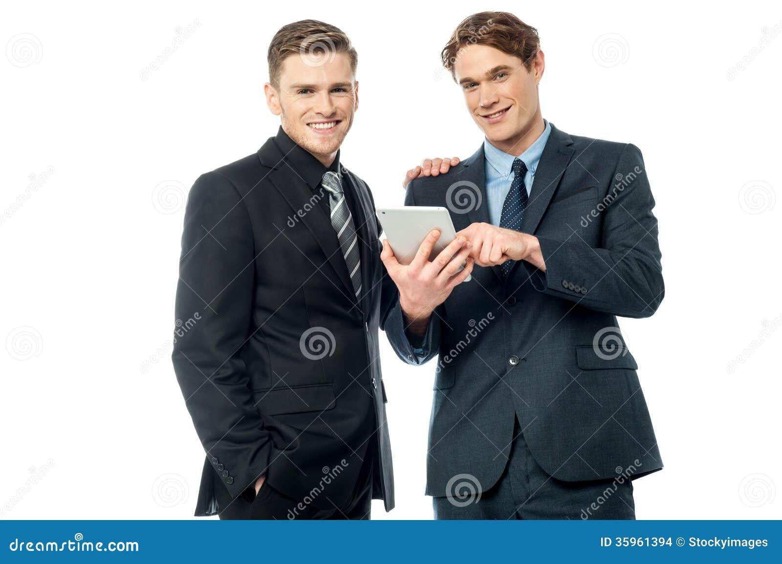 Hombres de negocios que hojean en el dispositivo de la tableta