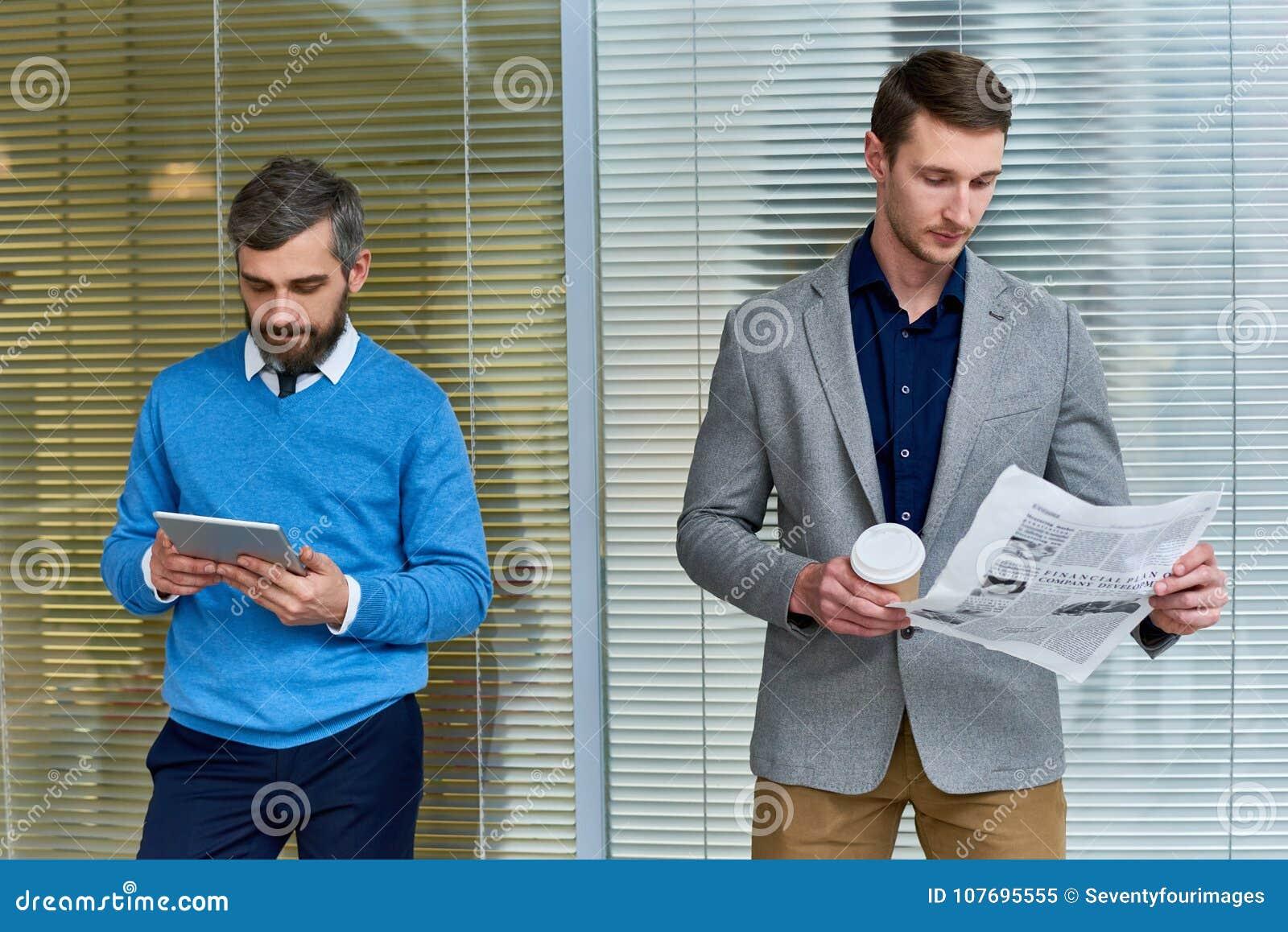 Hombres de negocios que leen en oficina