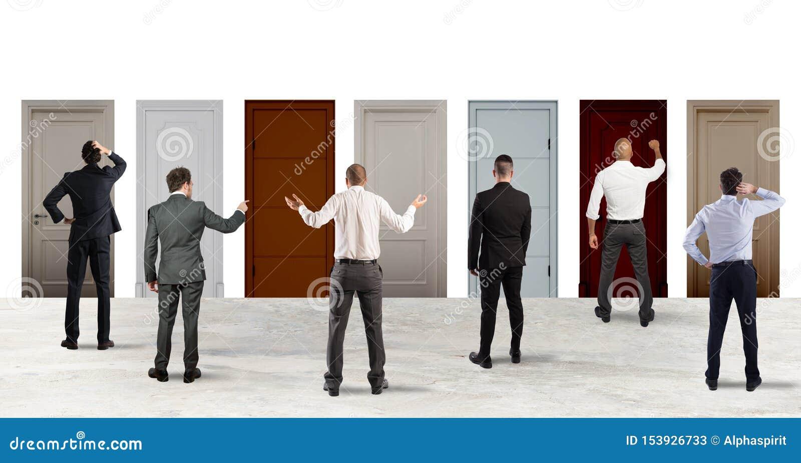 Hombres de negocios que miran para seleccionar la puerta a la derecha Concepto de confusión y de competencia