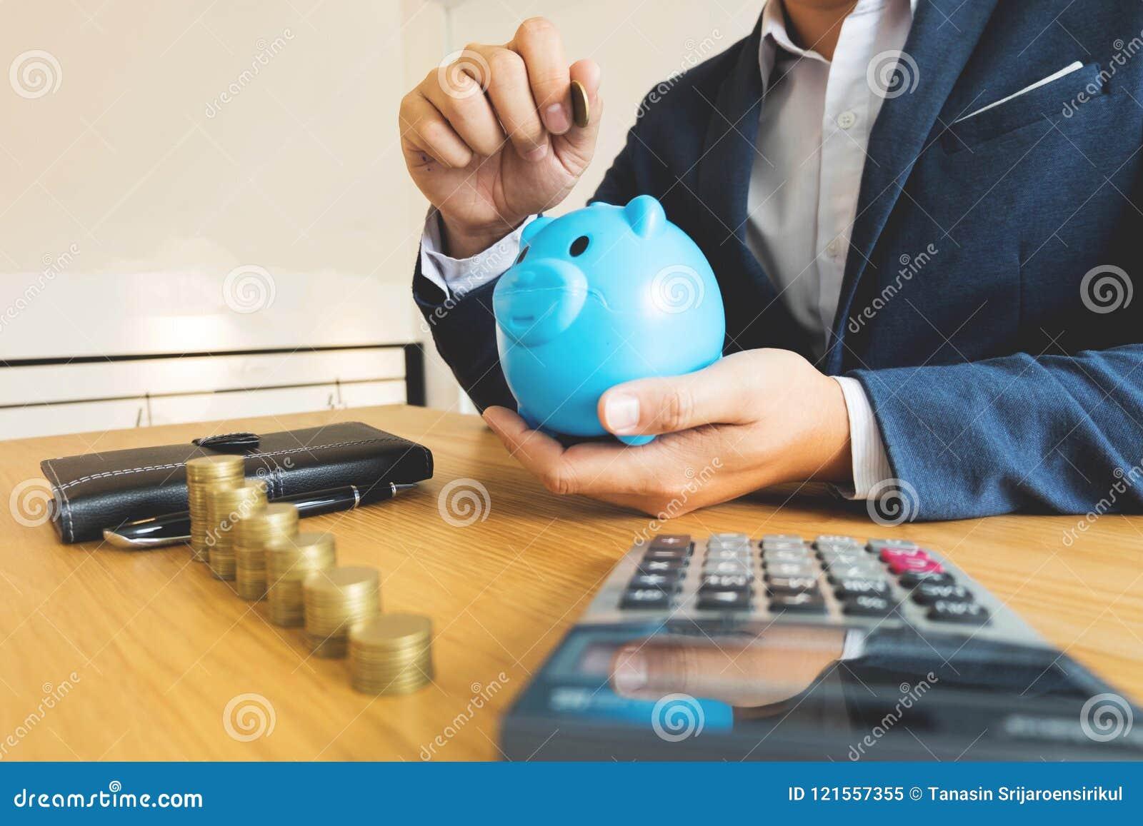 Hombres de negocios que ponen la moneda en la hucha azul, dinero de ahorro finan