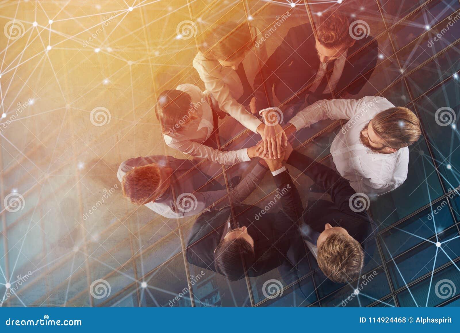 Hombres de negocios que ponen sus manos así como efectos del Internet Concepto de integración, trabajo en equipo y