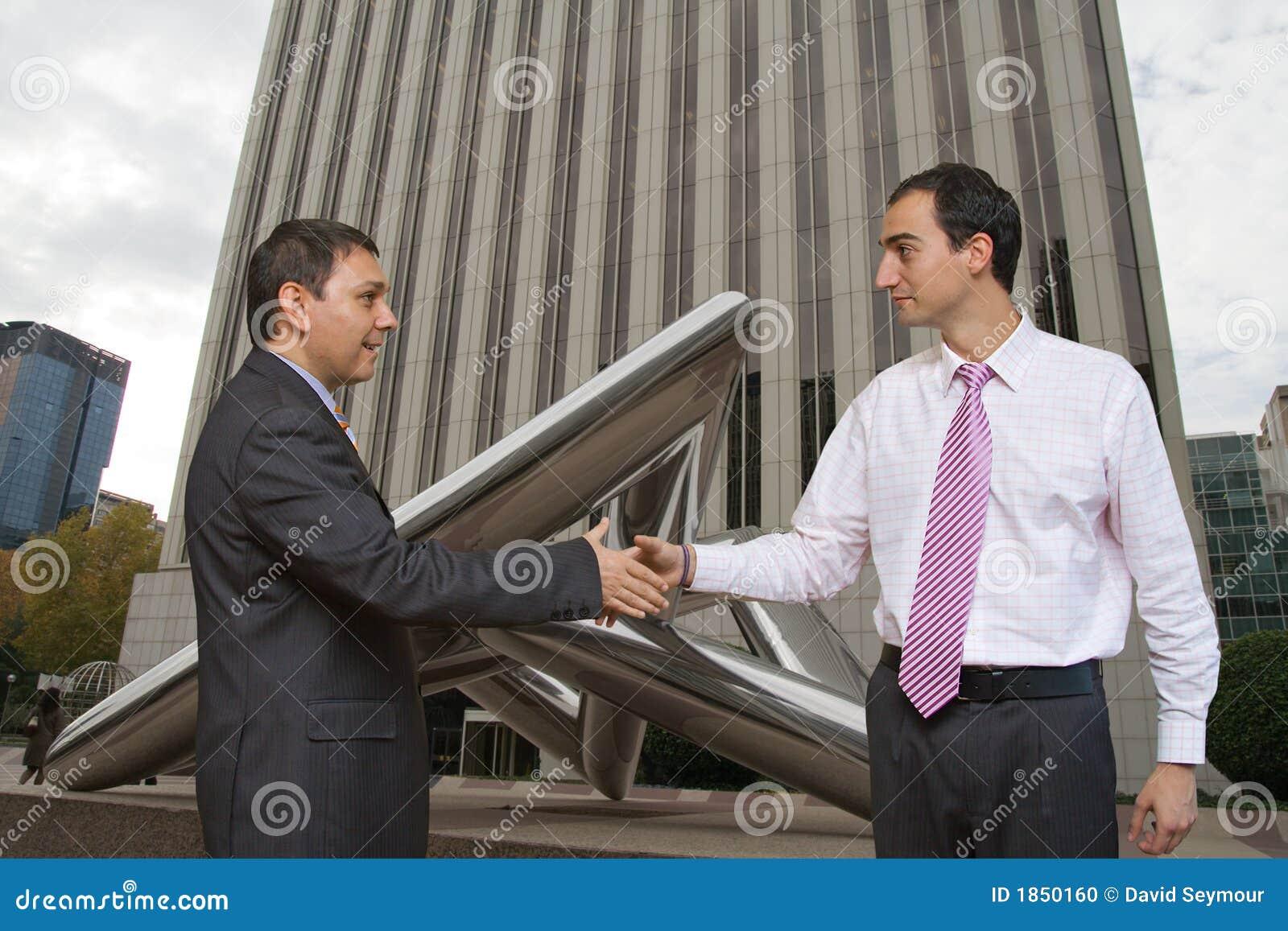Hombres de negocios que sacuden en un reparto