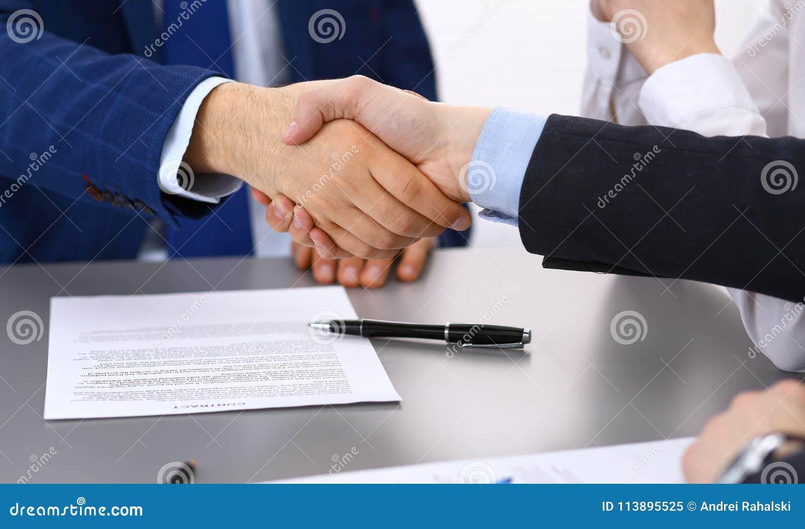 Hombres de negocios que sacuden las manos, acabando para arriba una firma de los papeles Concepto asesor de la reunión, del contr