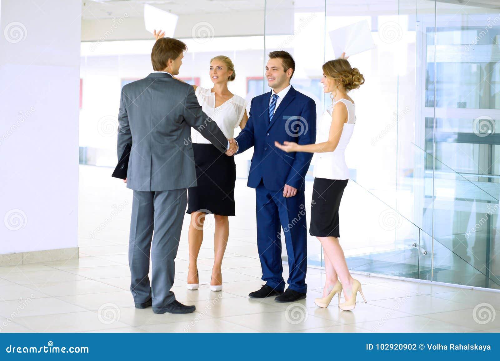 Hombres de negocios que sacuden las manos Dos hombres de negocios confiados que sacuden las manos y que sonríen mientras que se c