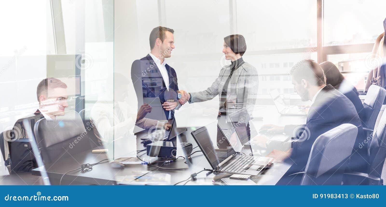 Hombres de negocios que sacuden las manos en oficina corporativa del moder