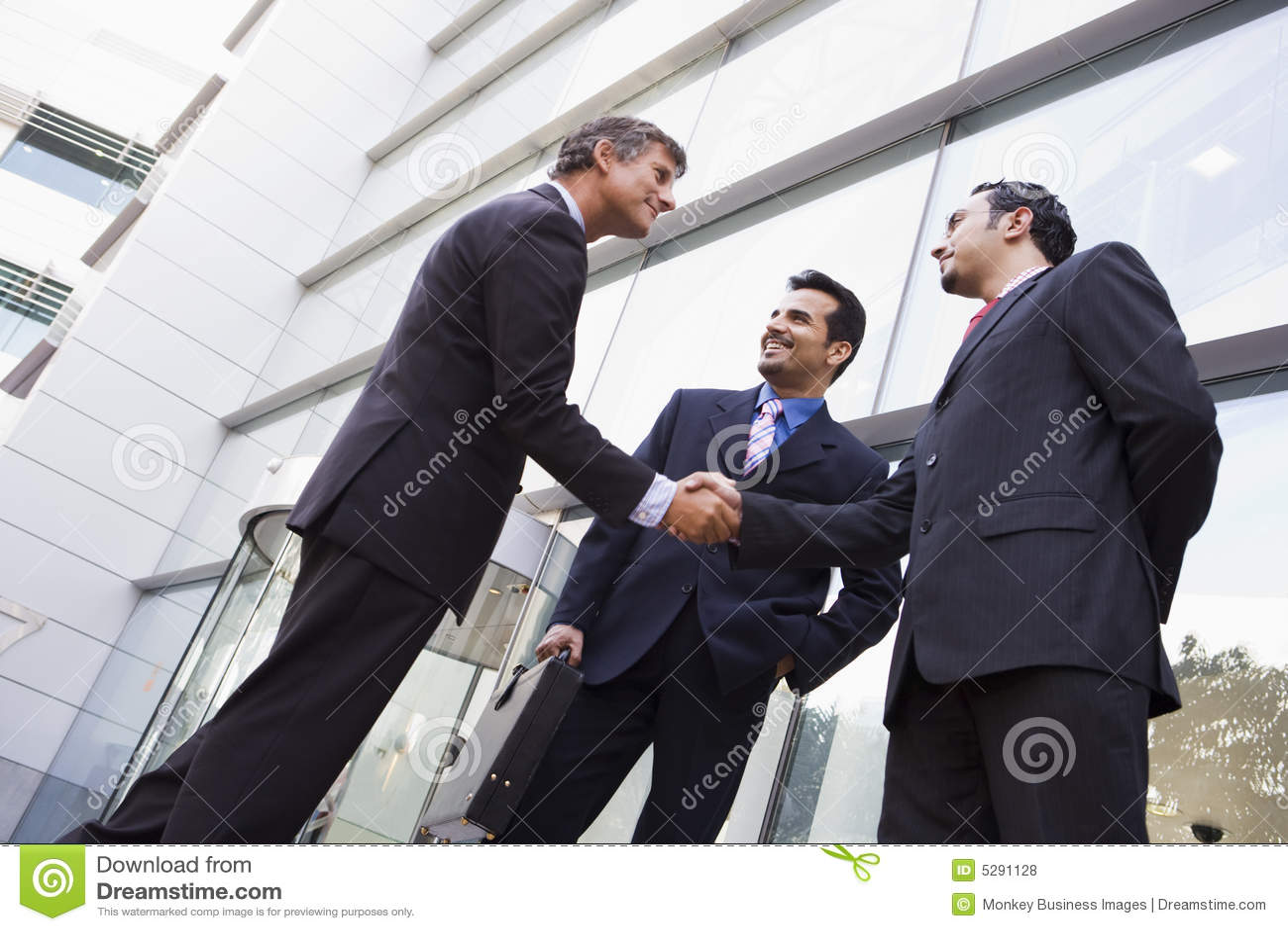 Hombres de negocios que sacuden las manos fuera de la oficina