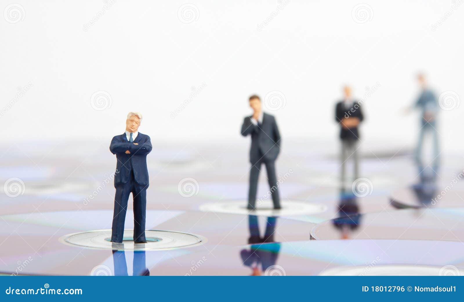 Hombres de negocios que se colocan en los Cdes del ordenador