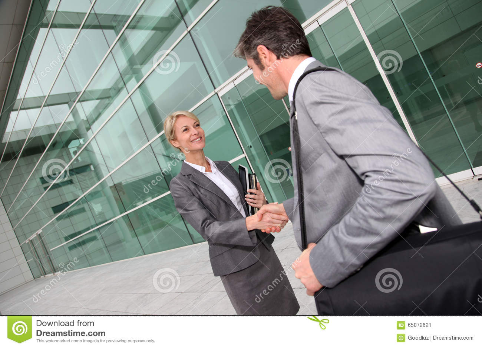 Hombres de negocios que se encuentran delante del edificio de oficinas