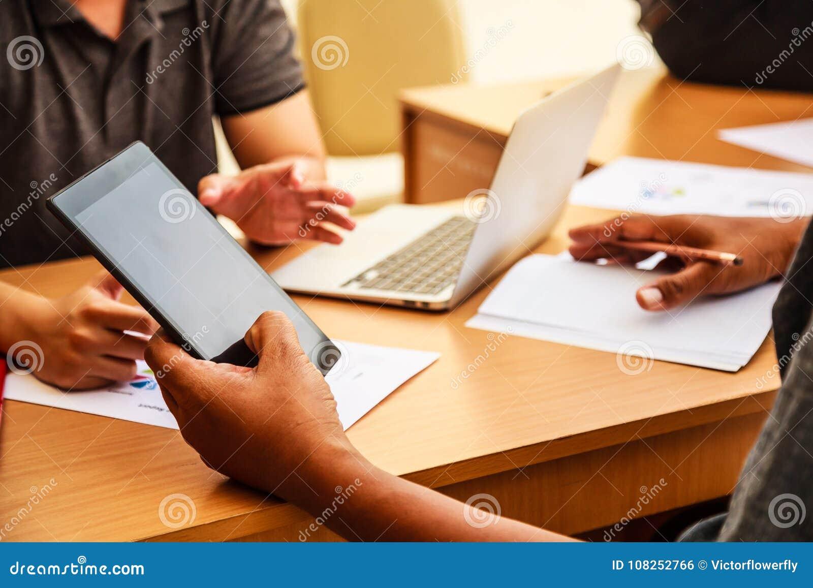 Hombres de negocios que se encuentran en el concepto de la oficina, usando ideas, cartas, ordenadores, tableta, dispositivos eleg