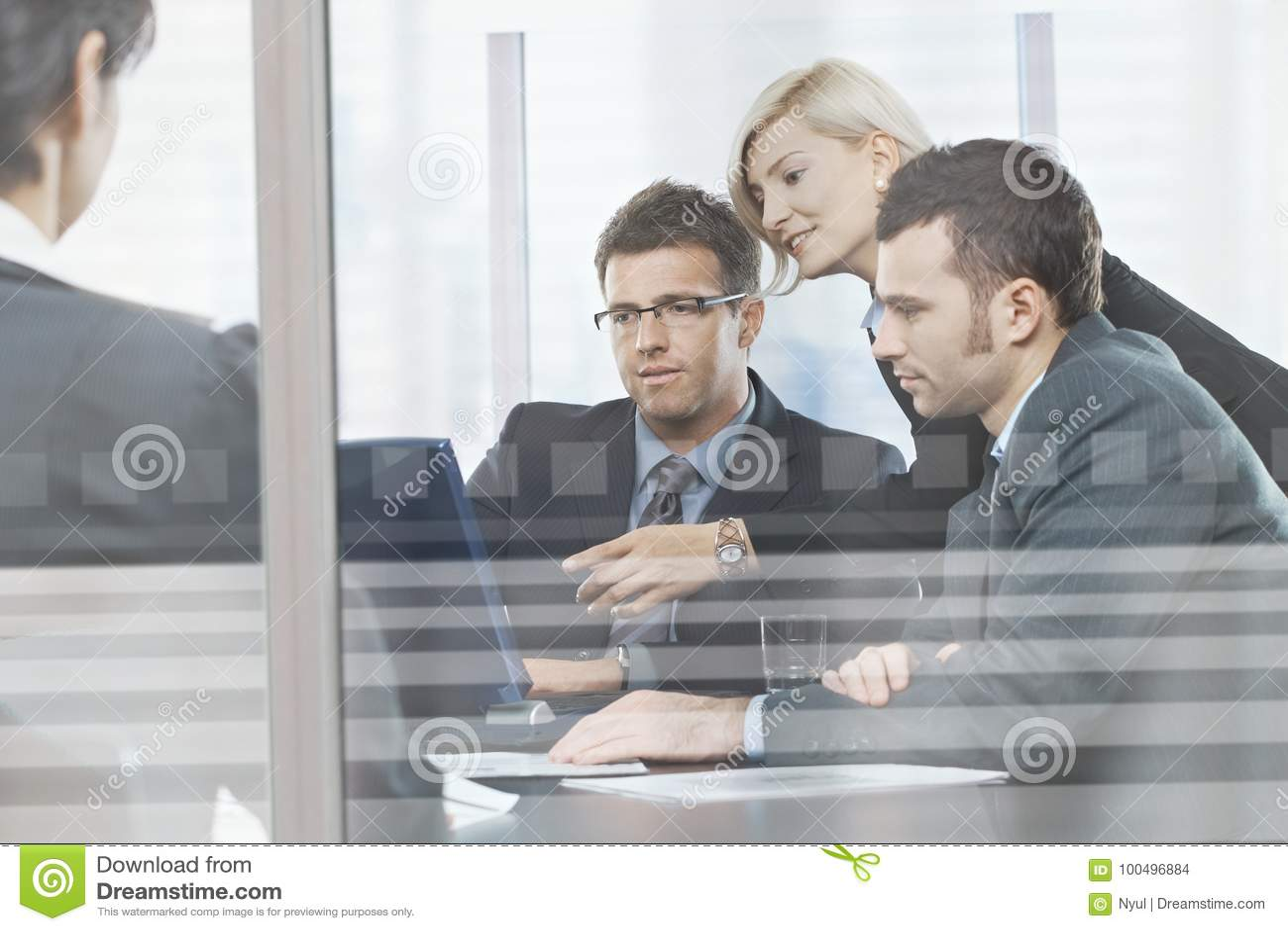 Hombres de negocios que se encuentran en la sala de reunión detrás del vidrio