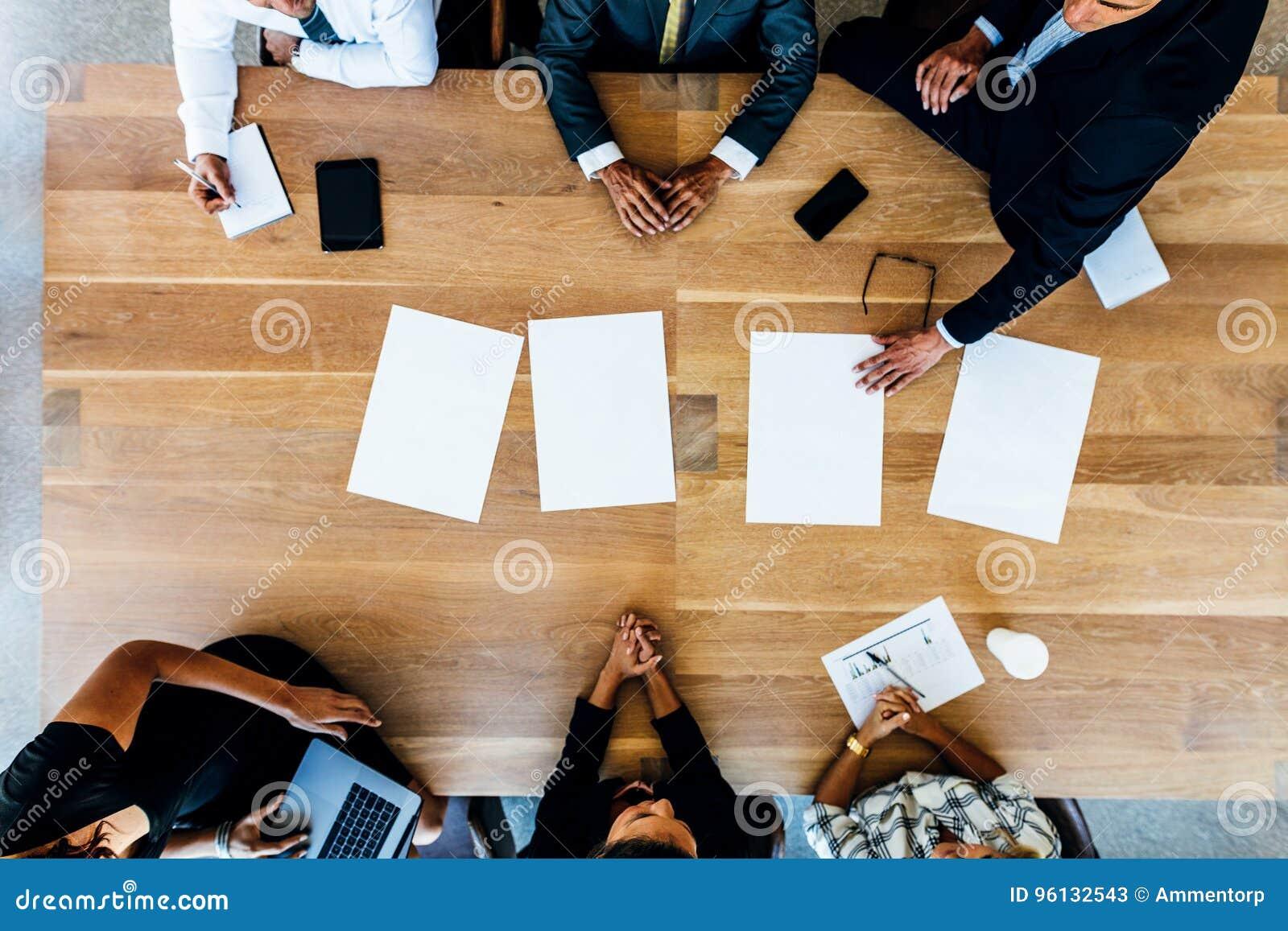 Hombres de negocios que se sientan alrededor de una tabla con las hojas en blanco