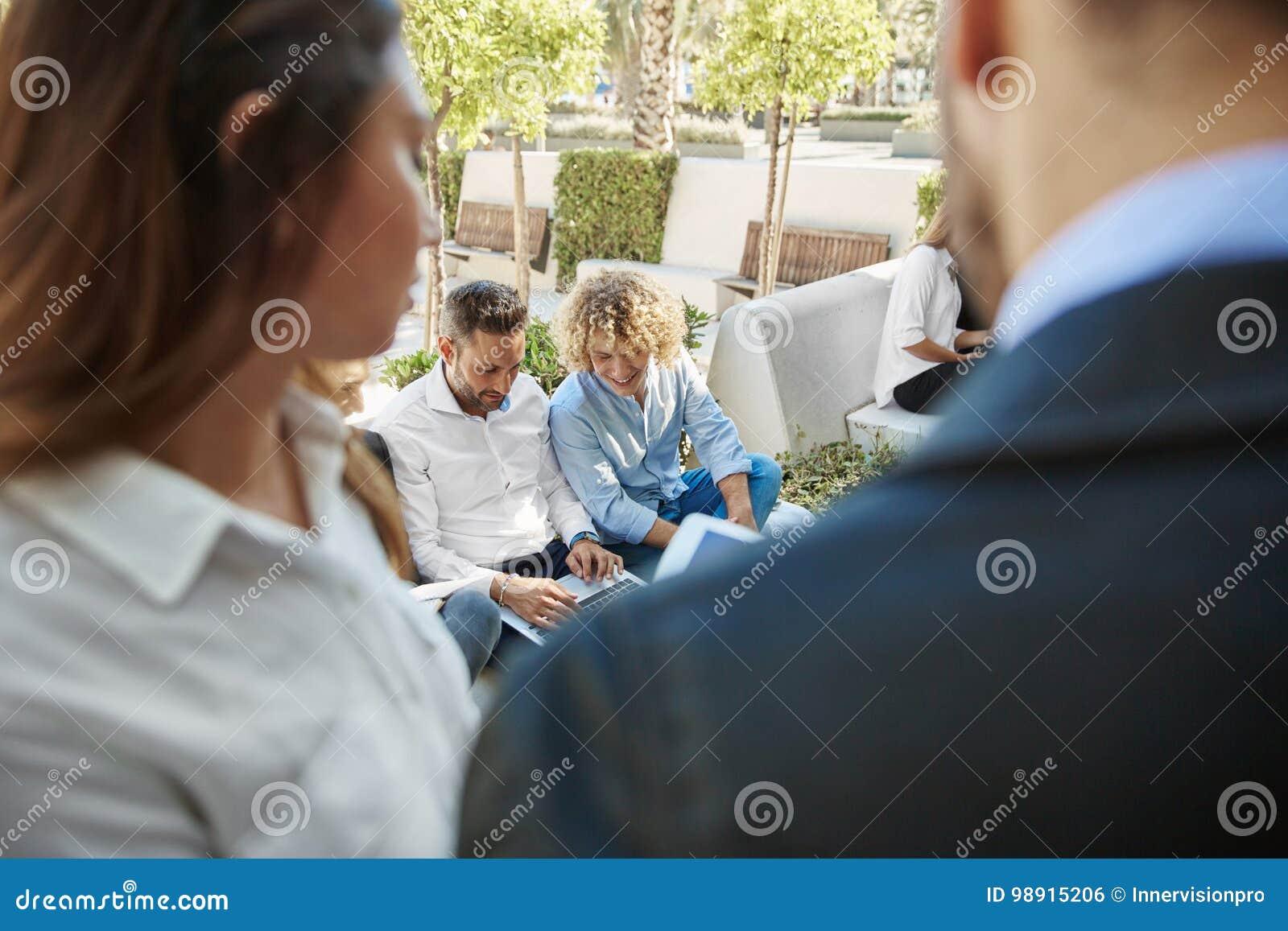 Hombres de negocios que sientan el exterior que trabaja junto en el ordenador portátil
