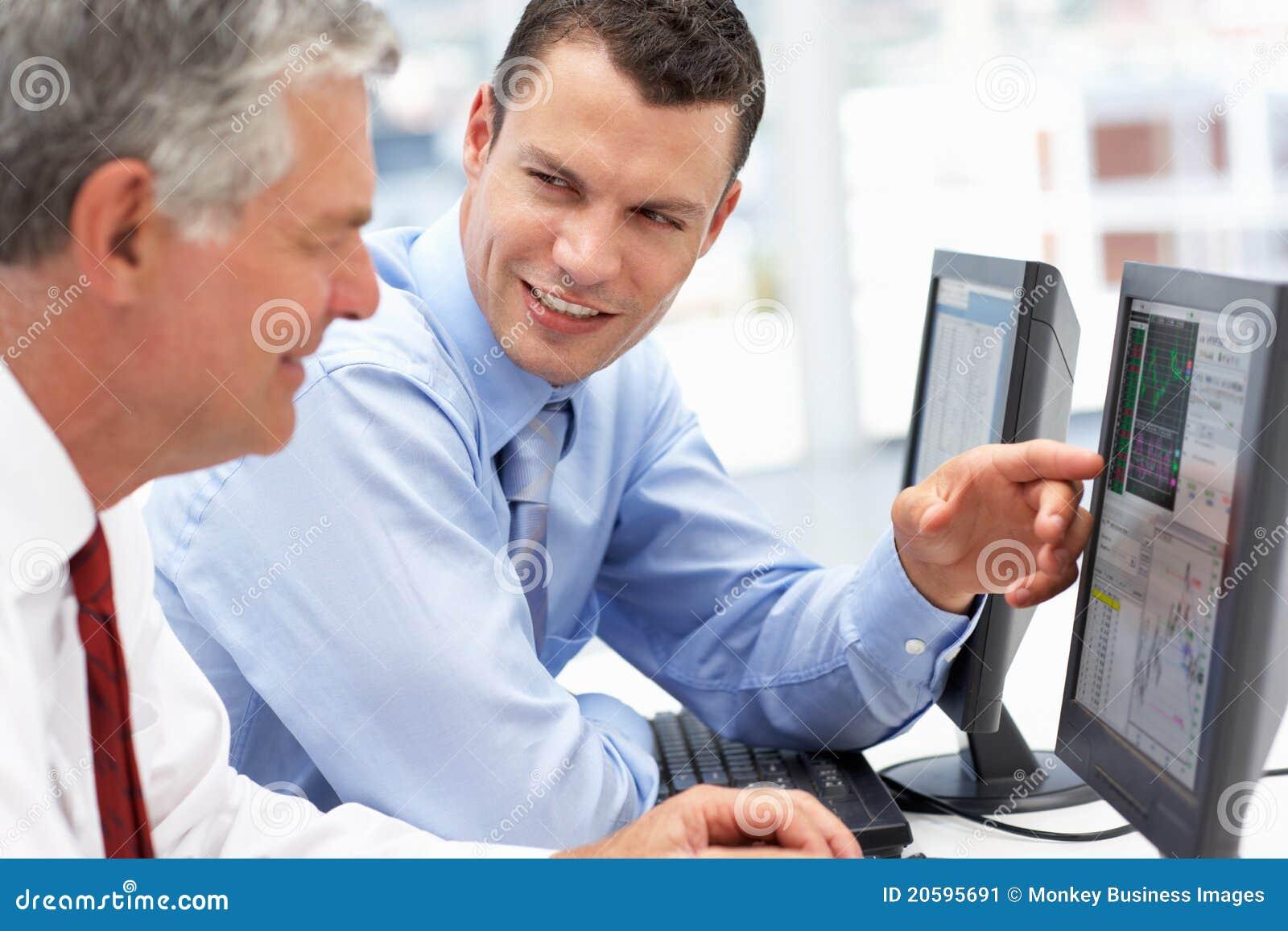 Hombres de negocios que trabajan en los ordenadores