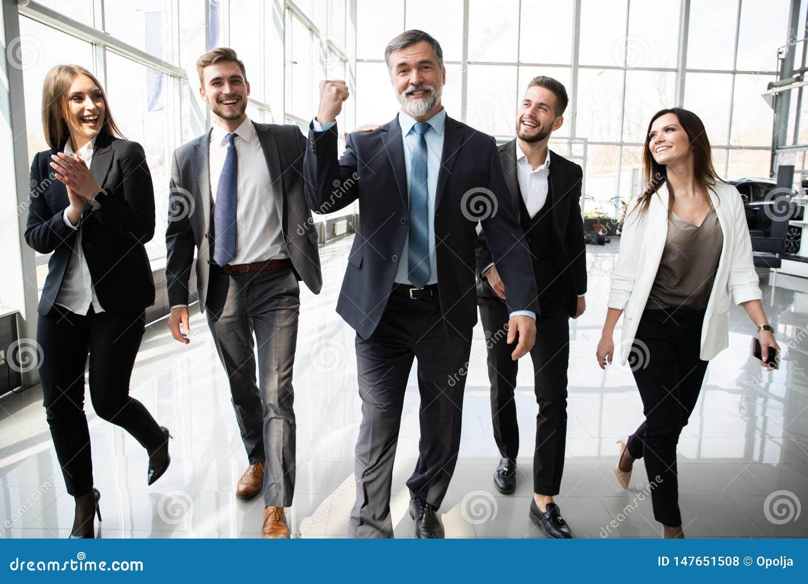 Hombres de negocios de Team Walking In Modern Office, hombres de negocios confiados y empresarias con el l?der maduro In Foregrou