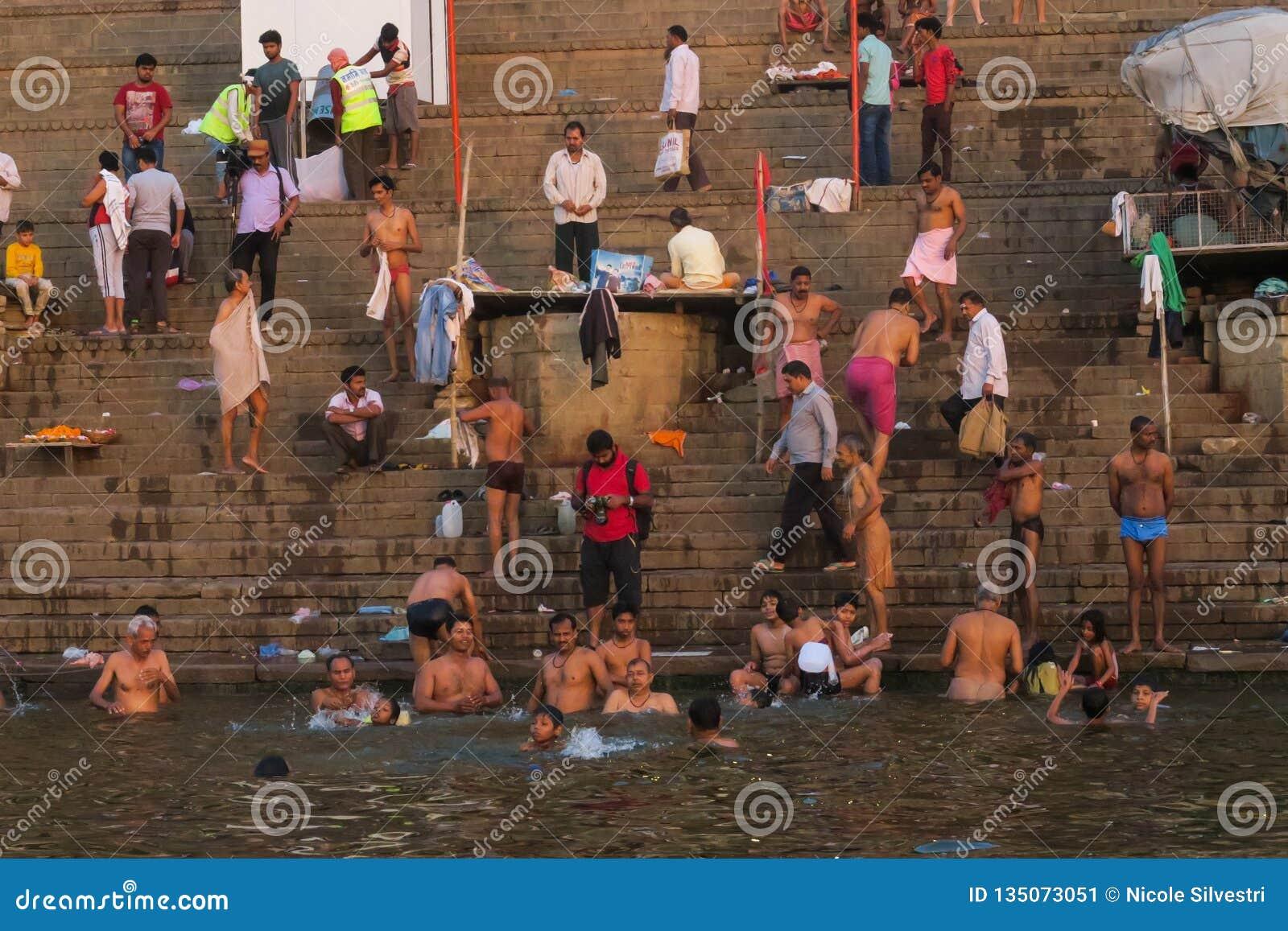 Hombres jovenes que nadan en el río del Ganges como tradición religiosa