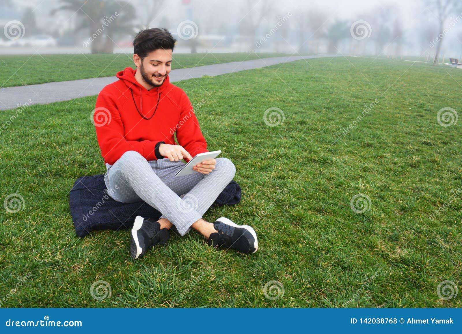 Hombres jovenes usando la tableta digital en parque público