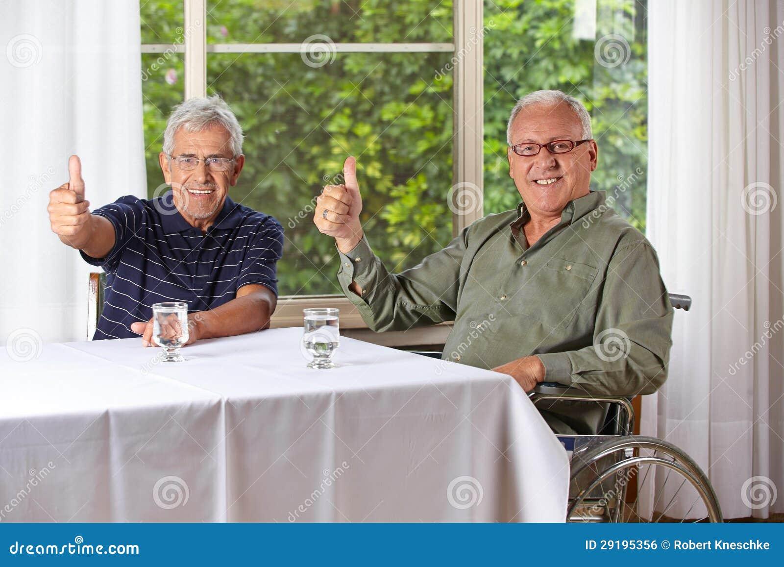 Hombres mayores felices que detienen los pulgares