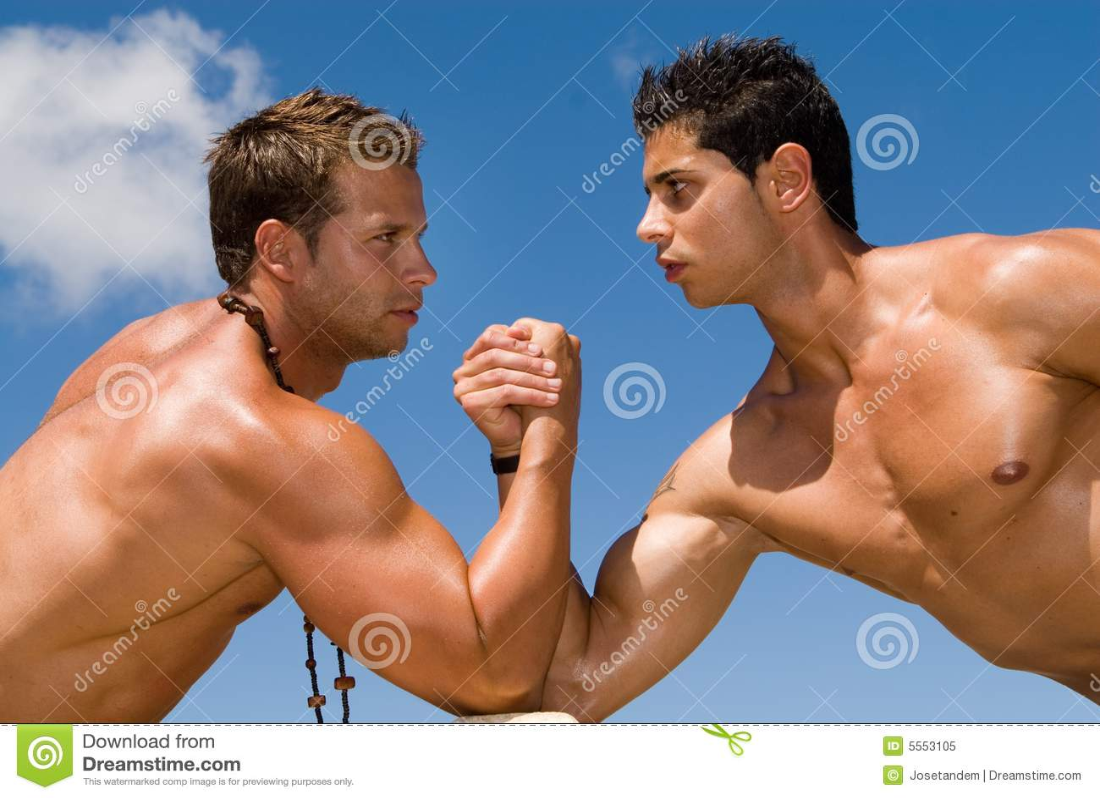 ... de archivo libre de regalías: Hombres musculosos bajo el cielo azul