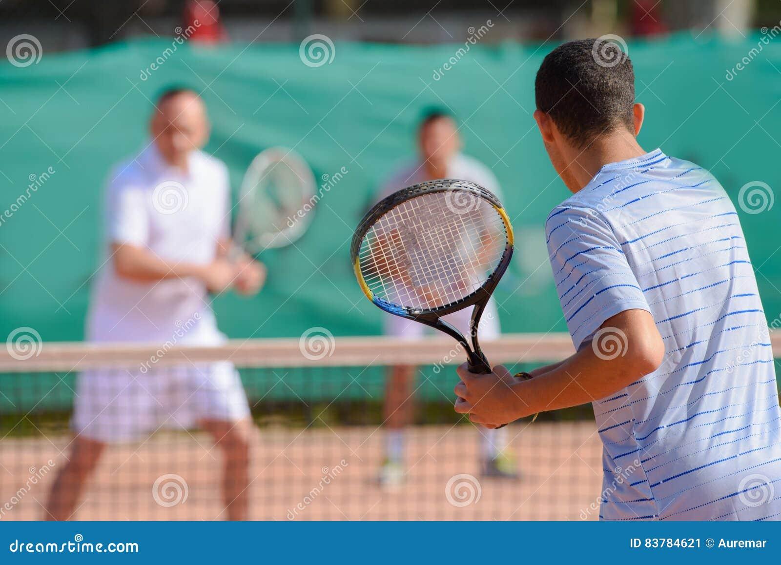 Hombres que juegan a tenis del juego de los dobles