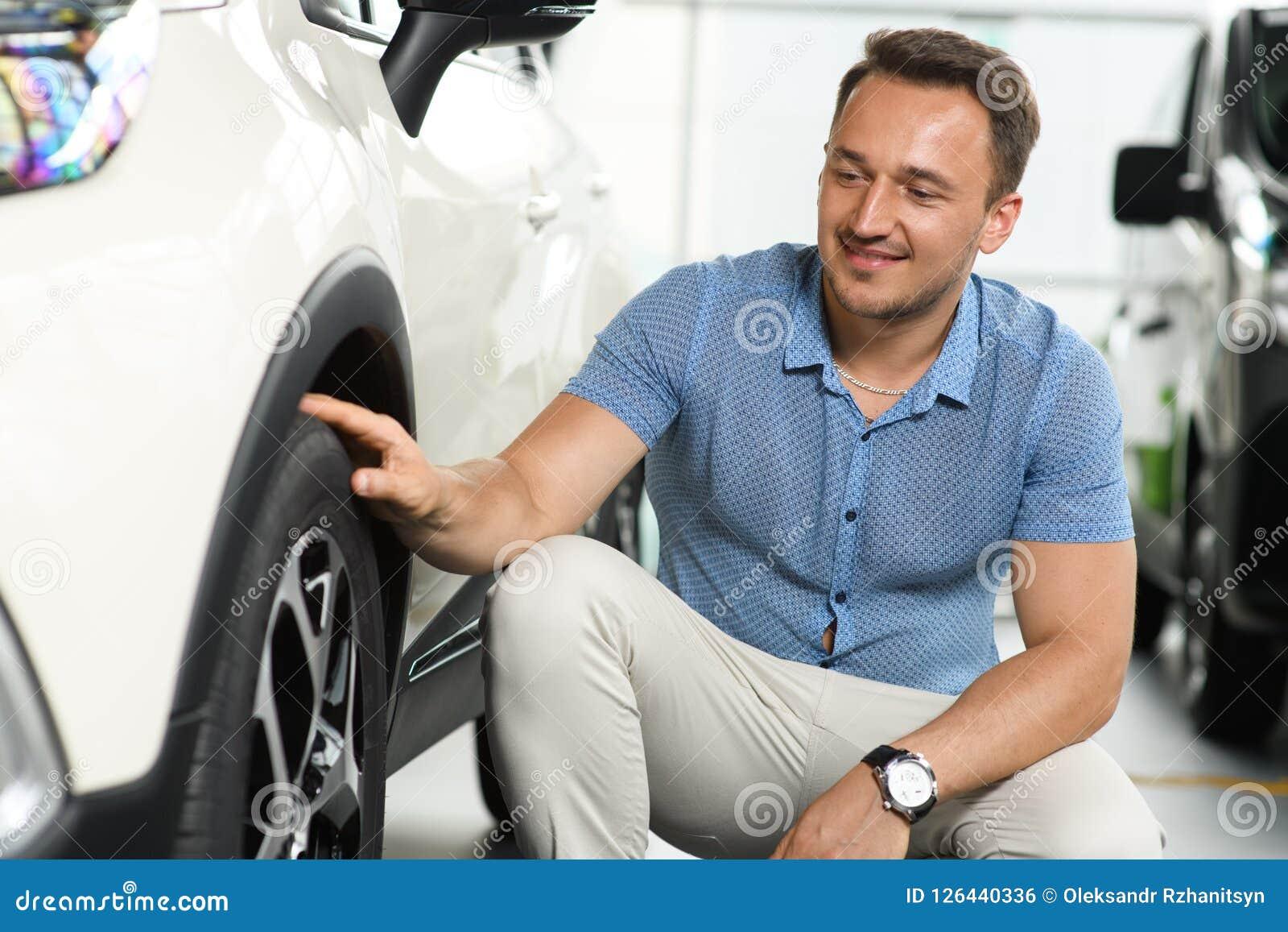 Hombres que tocan la rueda de coche