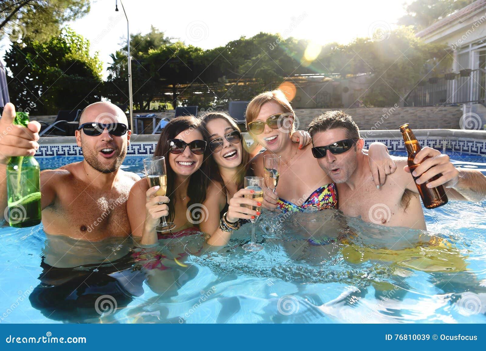 Hombres y mujeres atractivos felices en el bikini que tiene baño en la cerveza de consumición de la piscina del centro turístico