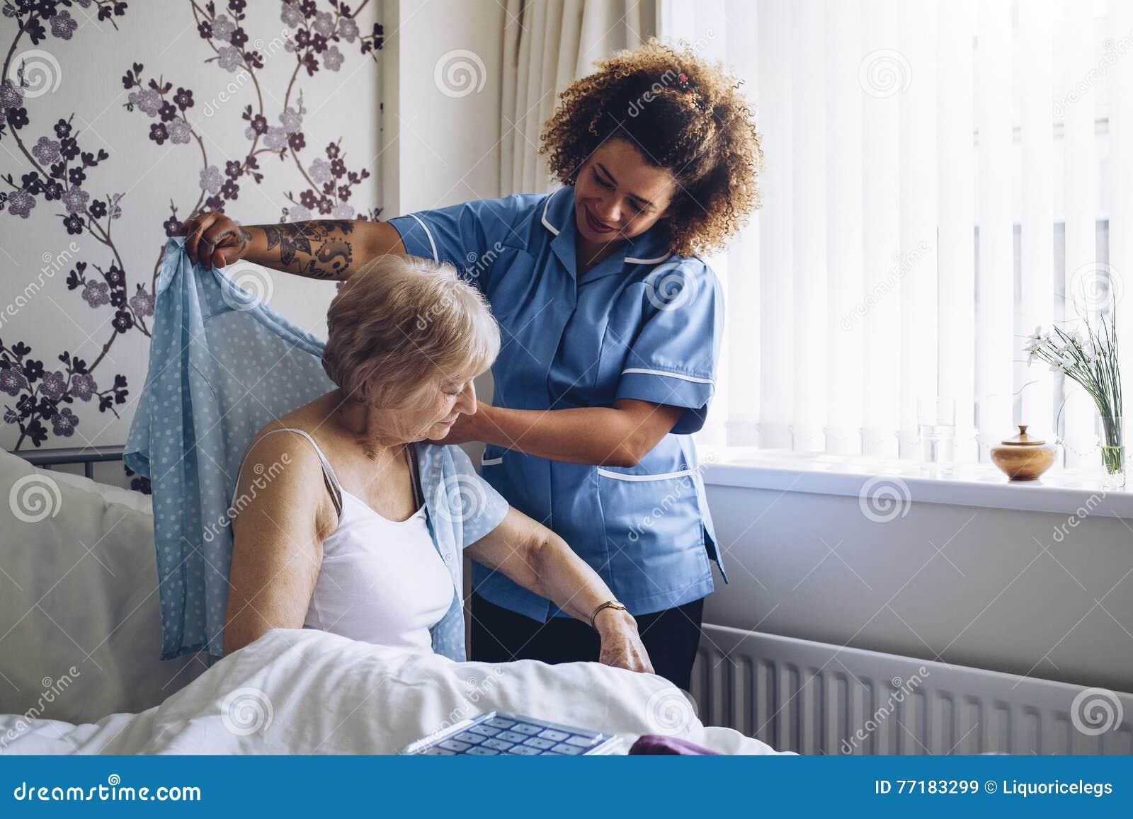 home caregiver dressing senior stock photo image 77183299. Black Bedroom Furniture Sets. Home Design Ideas