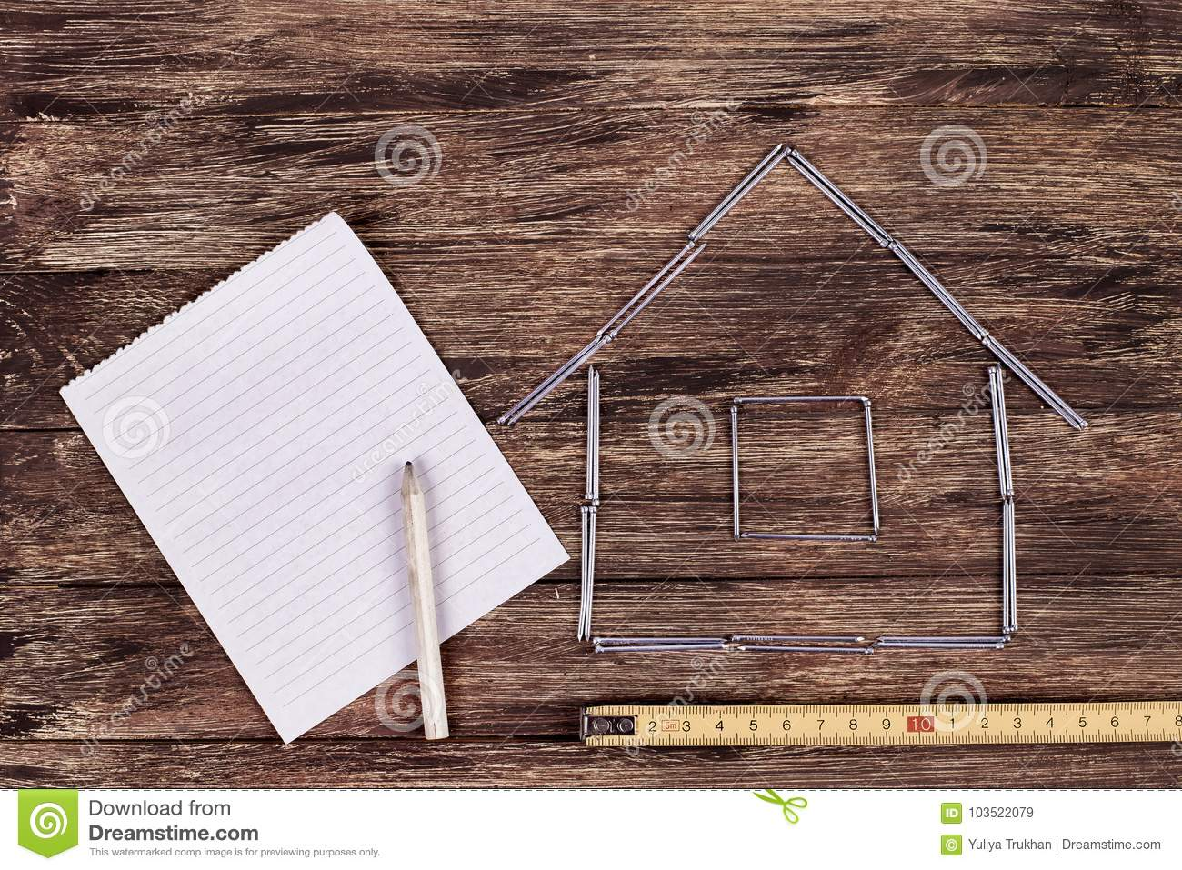 Home concept. Wooden model house on a work table with tools and empty spiral notebook